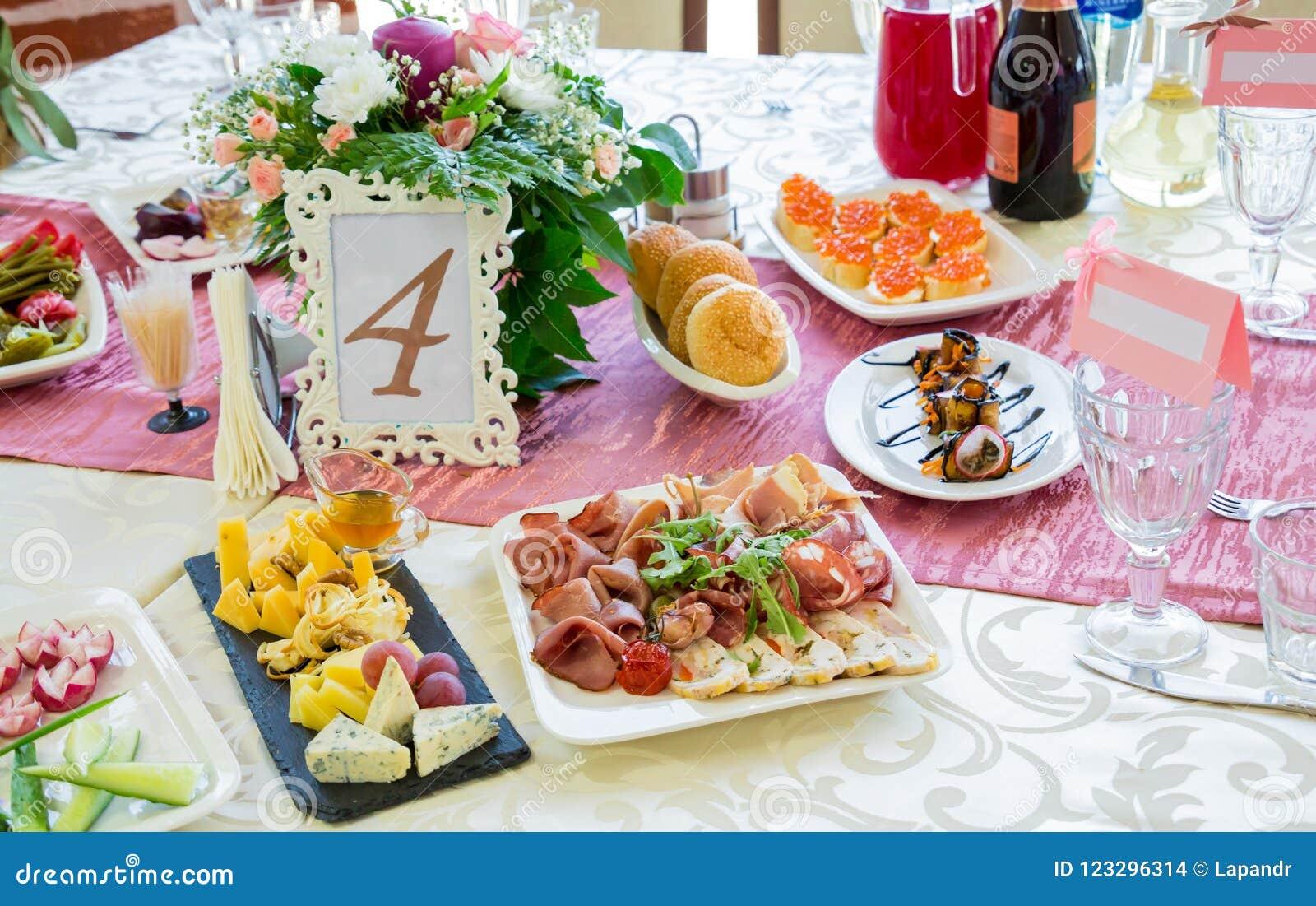 Εξυπηρετούμενοι πίνακες στο συμπόσιο Ποτά, πρόχειρα φαγητά, λιχουδιές και λουλούδια στο εστιατόριο Ένα γεγονός ή ένας γάμος gala