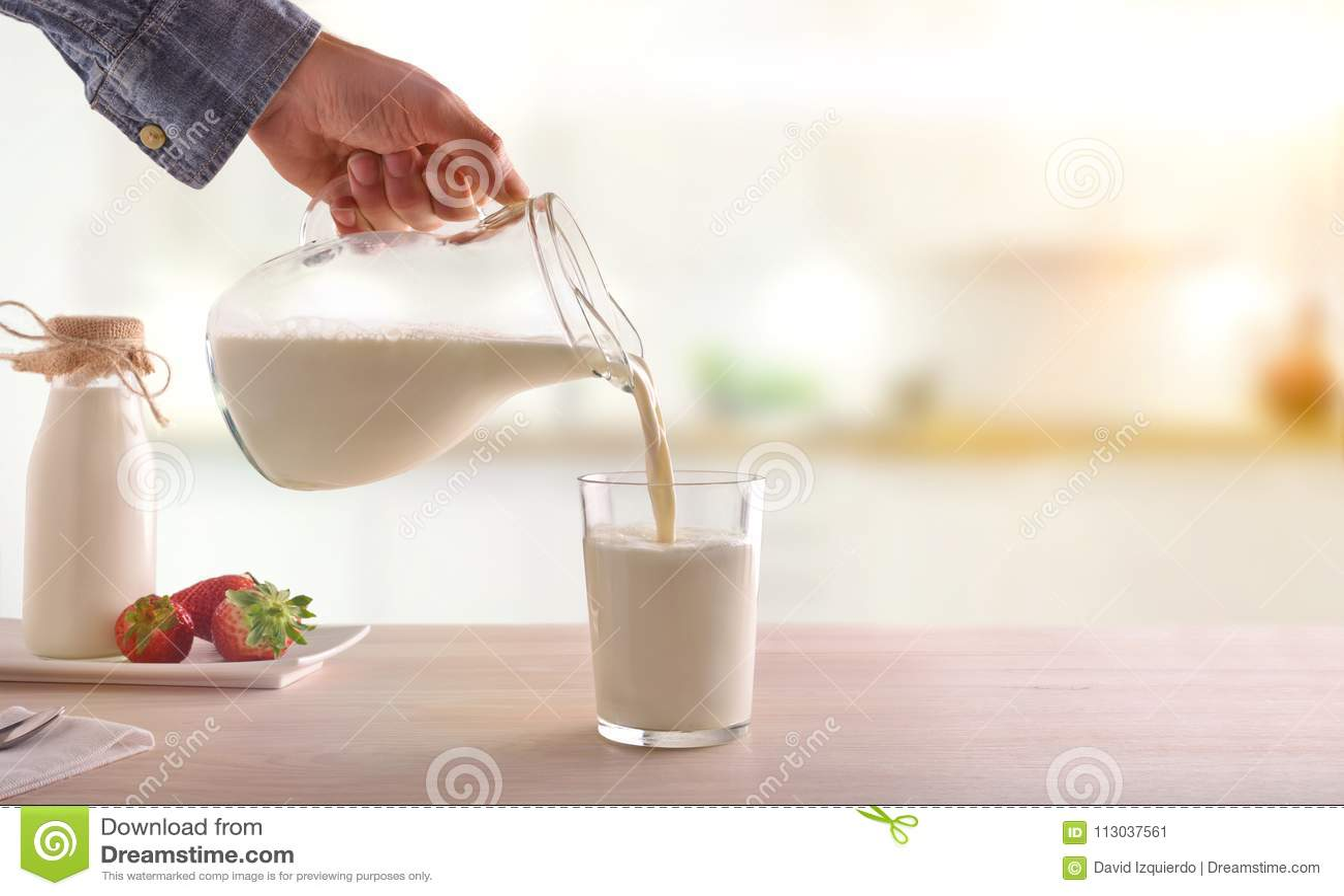 Εξυπηρετώντας γάλα προγευμάτων με μια κανάτα σε ένα γυαλί σε ένα άσπρο ξύλινο Κ