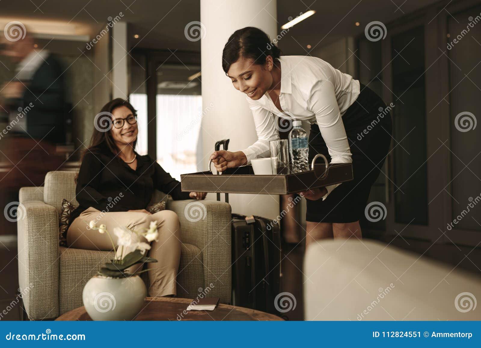 Εξυπηρετώντας καφές σερβιτορών σαλονιών αερολιμένων στο θηλυκό επιβάτη