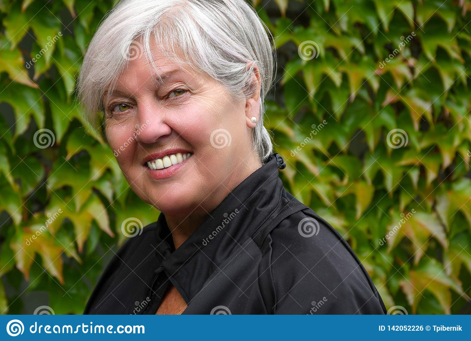 Εξωτερικό συμπαθητικό να φανεί χαμόγελου ηλικιωμένο ανώτερο πορτρέτο γυναικών με τον πράσινο τοίχο φύλλων