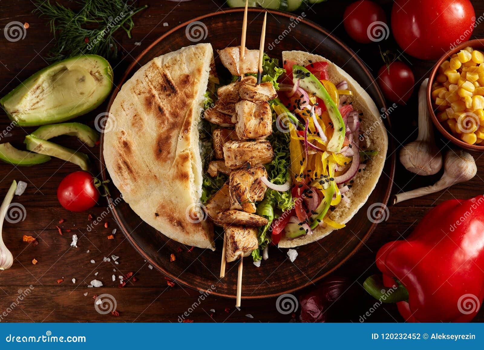 Εξωτικός ακόμα slife με το pita, φρέσκα λαχανικά και kebab πέρα από το ξύλινο υπόβαθρο, εκλεκτική εστίαση