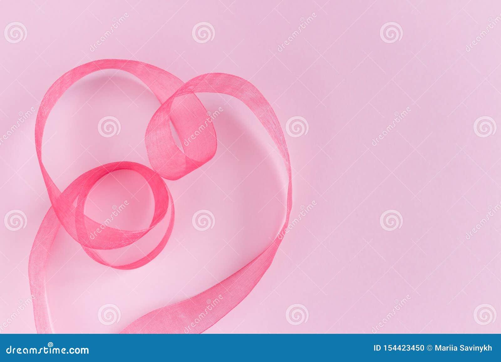 Εορταστικά ρόδινα κύματα κορδελλών μεταξιού σατέν στη μορφή καρδιών στο ρόδινο υπόβαθρο
