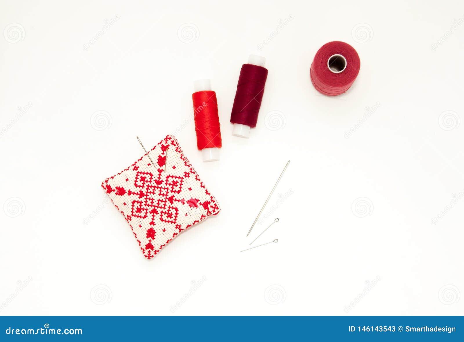 Επίπεδος βάλτε με το χειροποίητο κόκκινο κεντημένο μαξιλάρι βελόνων, στροφία νημάτων, καρφίτσες, βελόνες, χλεύη επάνω, τοπ άποψη