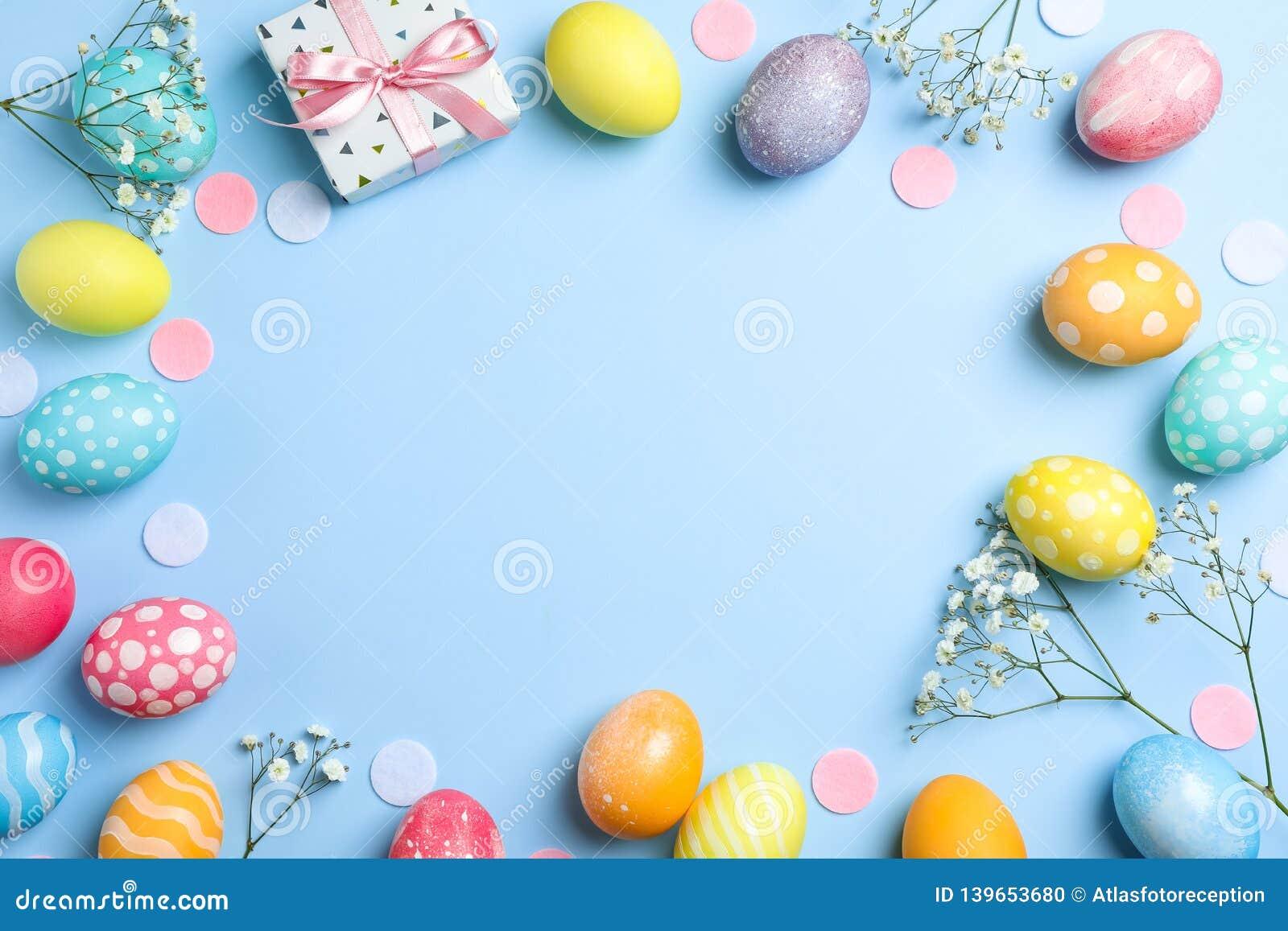 Επίπεδος βάλτε τη σύνθεση με τα αυγά Πάσχας, το παρόν και τα λουλούδια στο υπόβαθρο χρώματος, διάστημα για το κείμενο