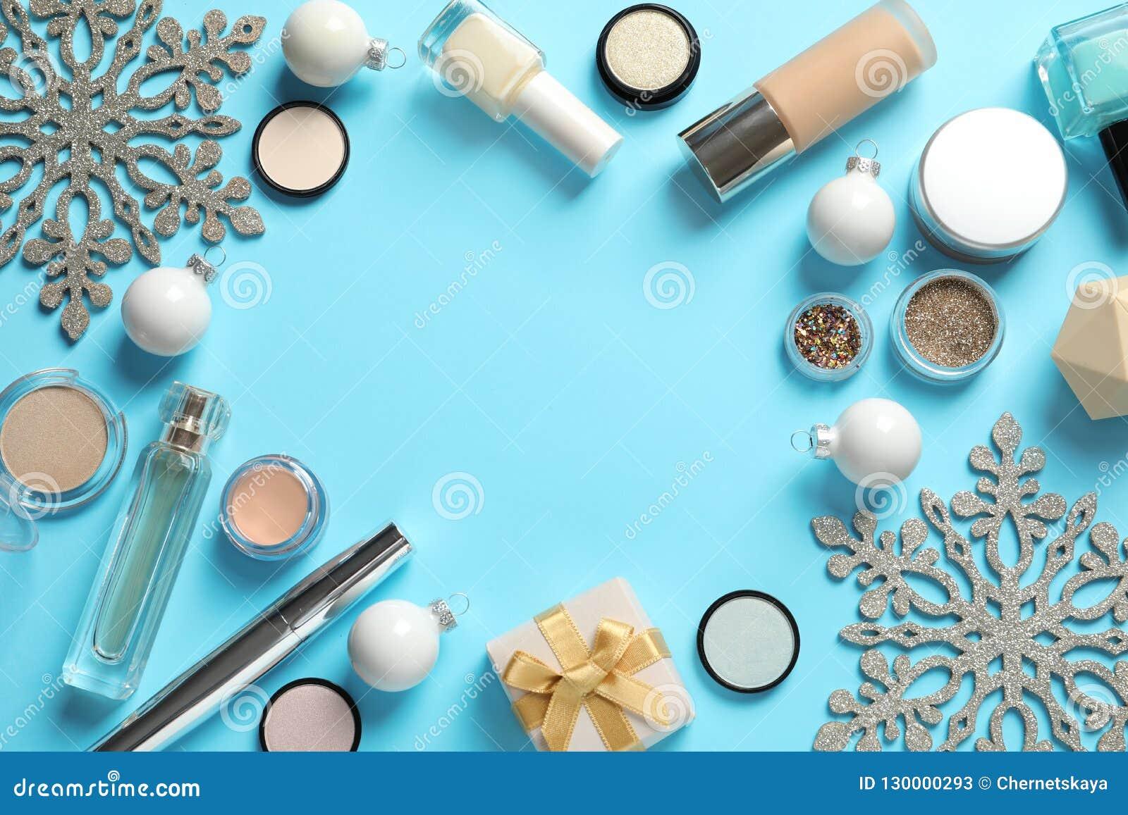 Επίπεδος βάλτε τη σύνθεση με τα προϊόντα makeup και το ντεκόρ Χριστουγέννων στο υπόβαθρο χρώματος