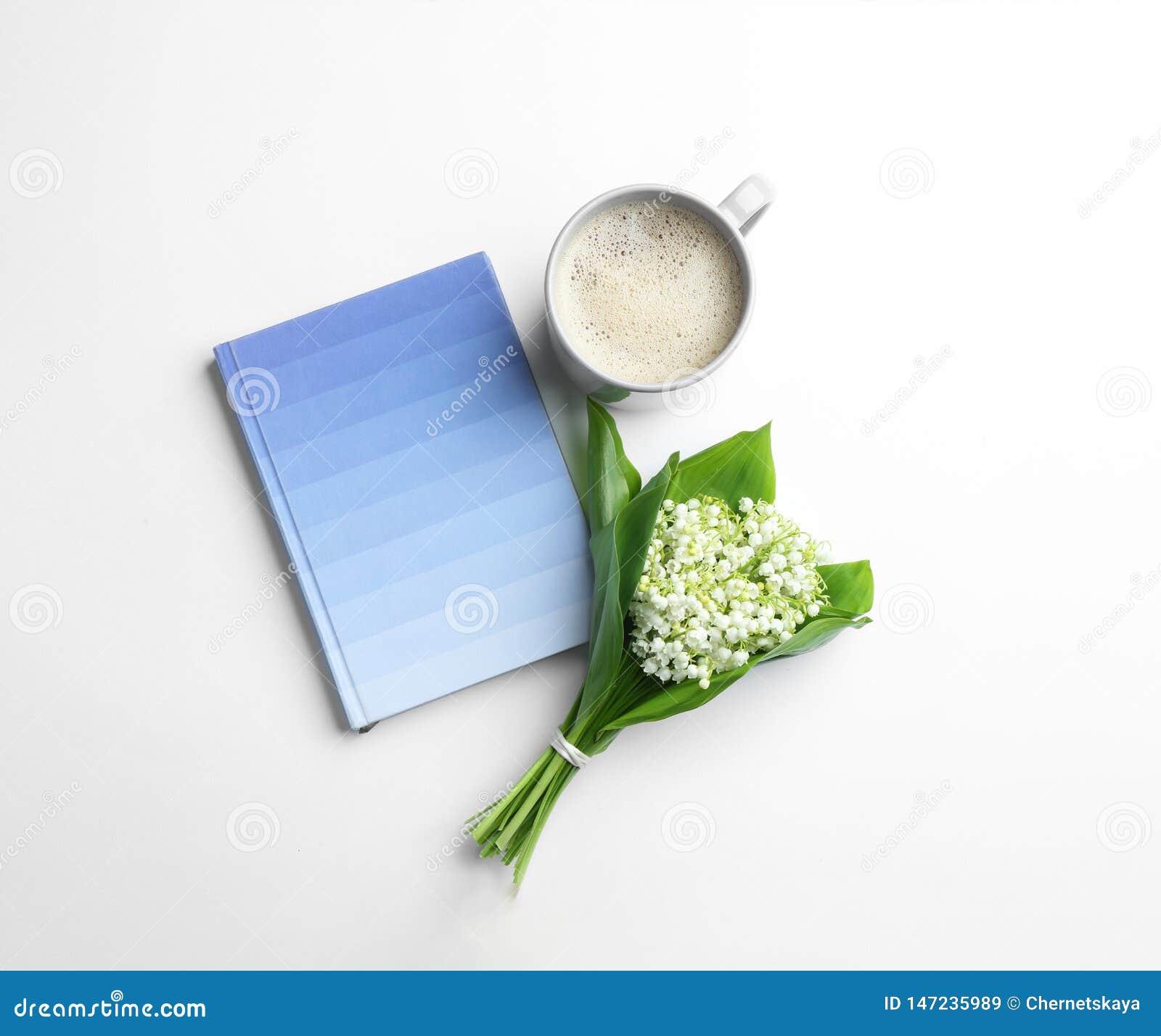 Επίπεδος βάλτε τη σύνθεση με το σημειωματάριο, τον κρίνο της ανθοδέσμης κοιλάδων και τον καφέ
