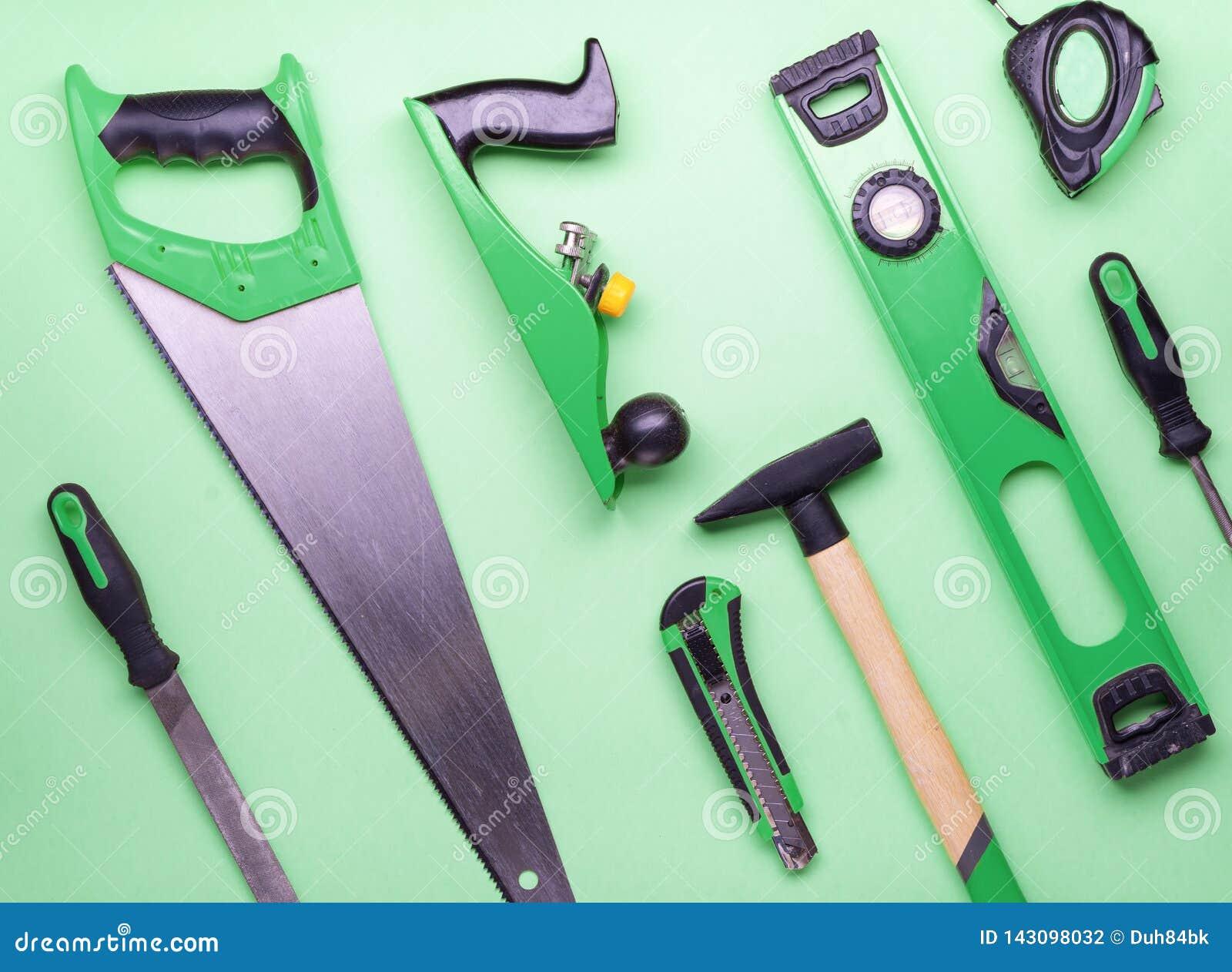 Επίπεδο σχεδιάγραμμα: ένα σύνολο εργαλείων χεριών για την κατασκευή και την επισκευή σε ένα πράσινο υπόβαθρο