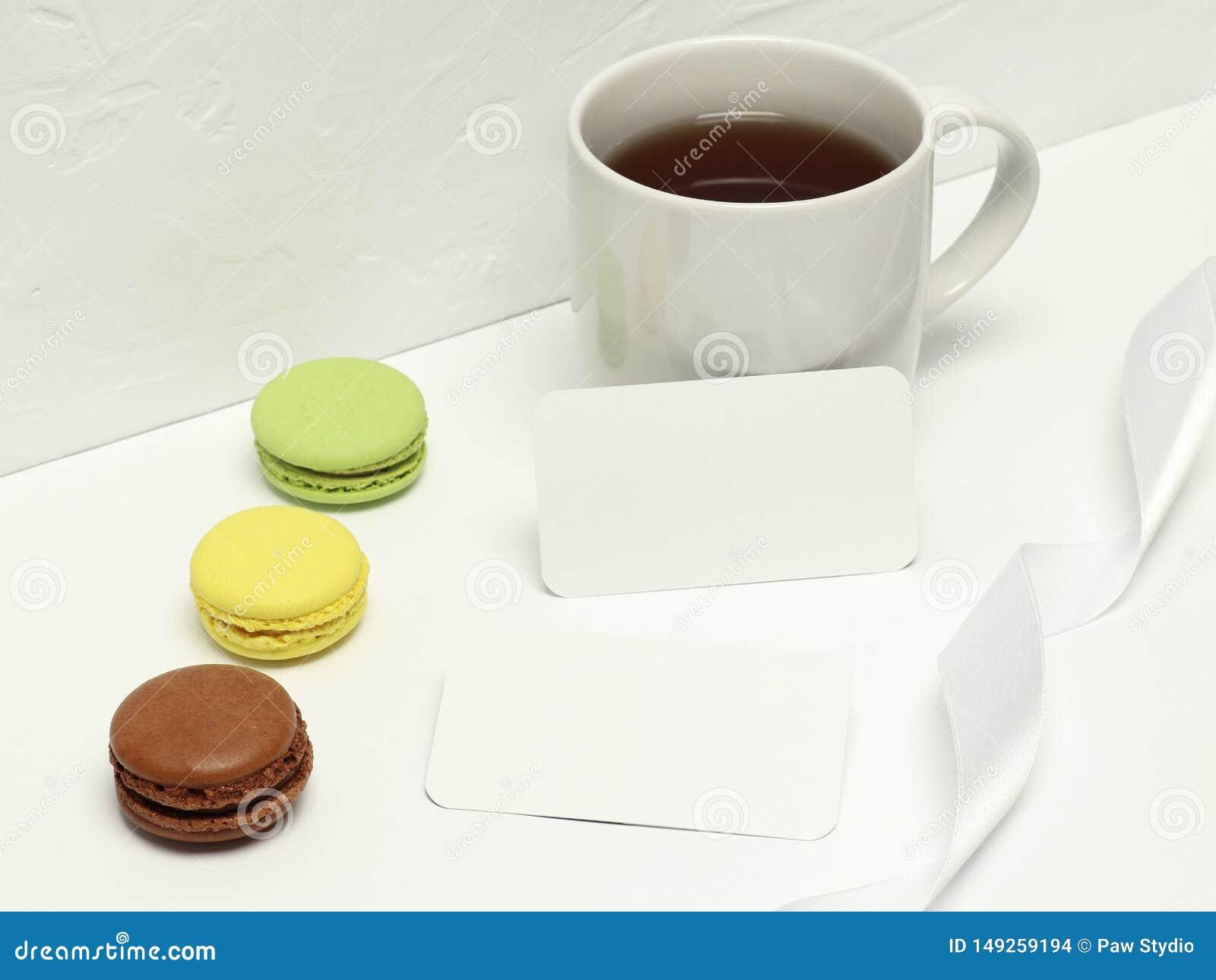Επαγγελματικές κάρτες προτύπων στο άσπρο υπόβαθρο με το macaron, την κορδέλλα και το φλιτζάνι του καφέ