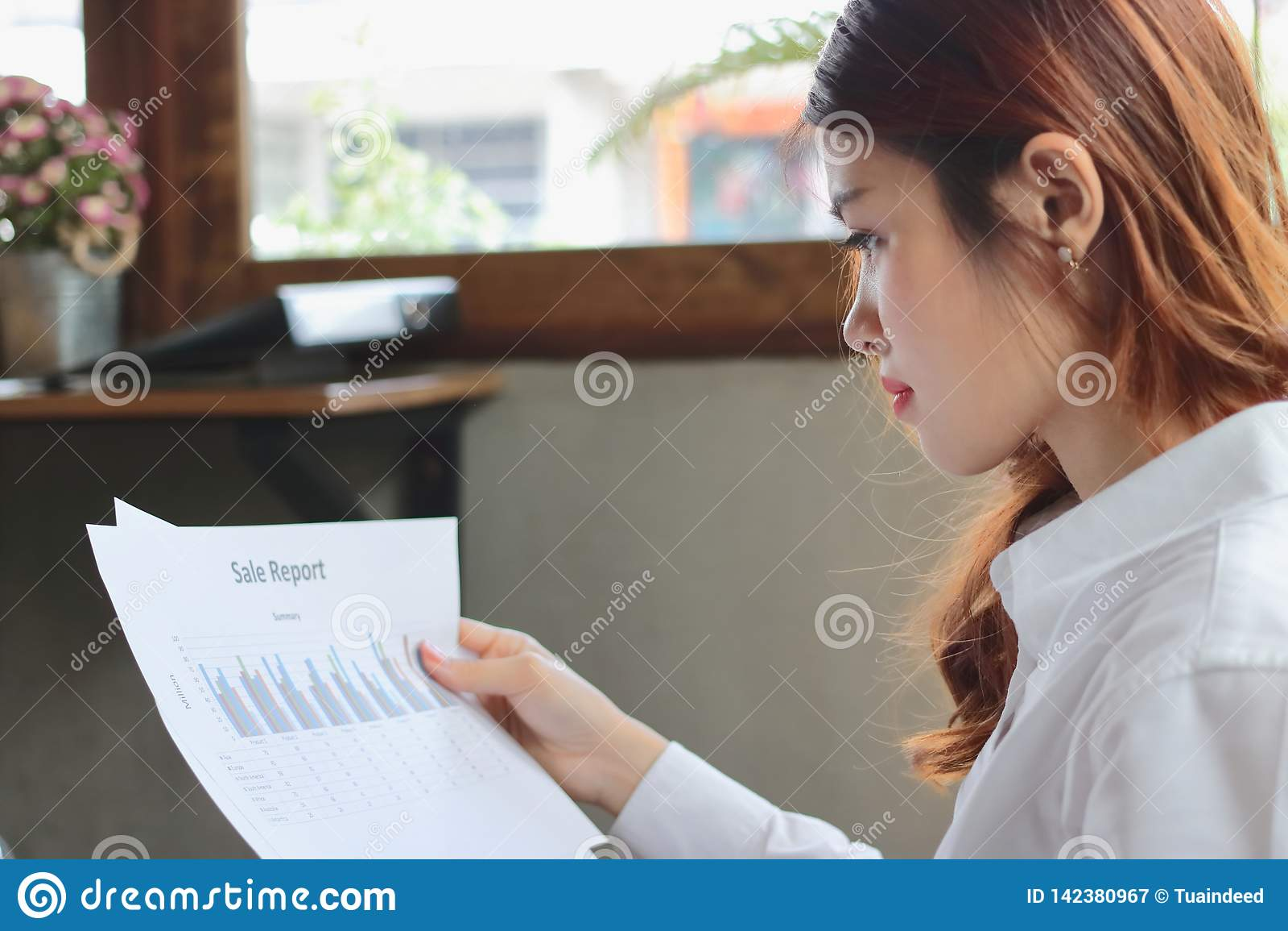 Επαγγελματική νέα ασιατική επιχειρησιακή γυναίκα που αναλύει τα διαγράμματα ή γραφική εργασία στην αρχή