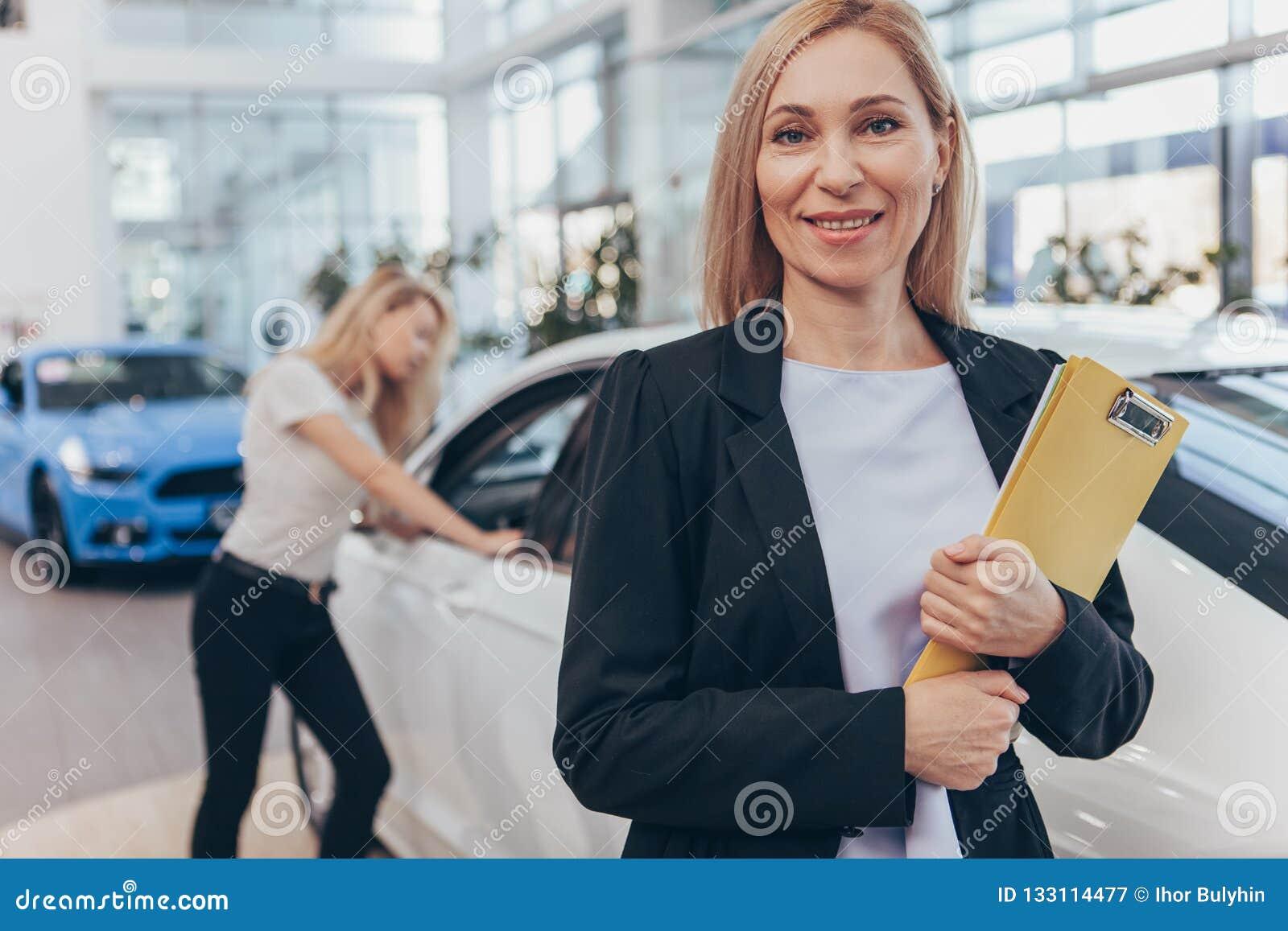 Επαγγελματικός έμπορος αυτοκινήτων που βοηθά το θηλυκό πελάτη της