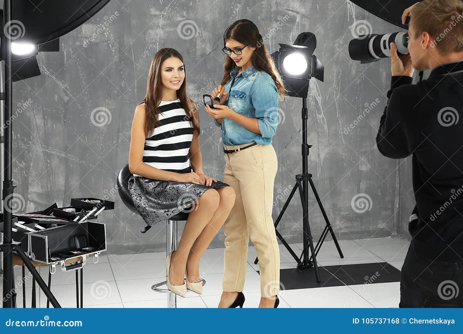 Επαγγελματικός καλλιτέχνης makeup που συνεργάζεται με τη νέα γυναίκα στο πυροβολισμό φωτογραφιών