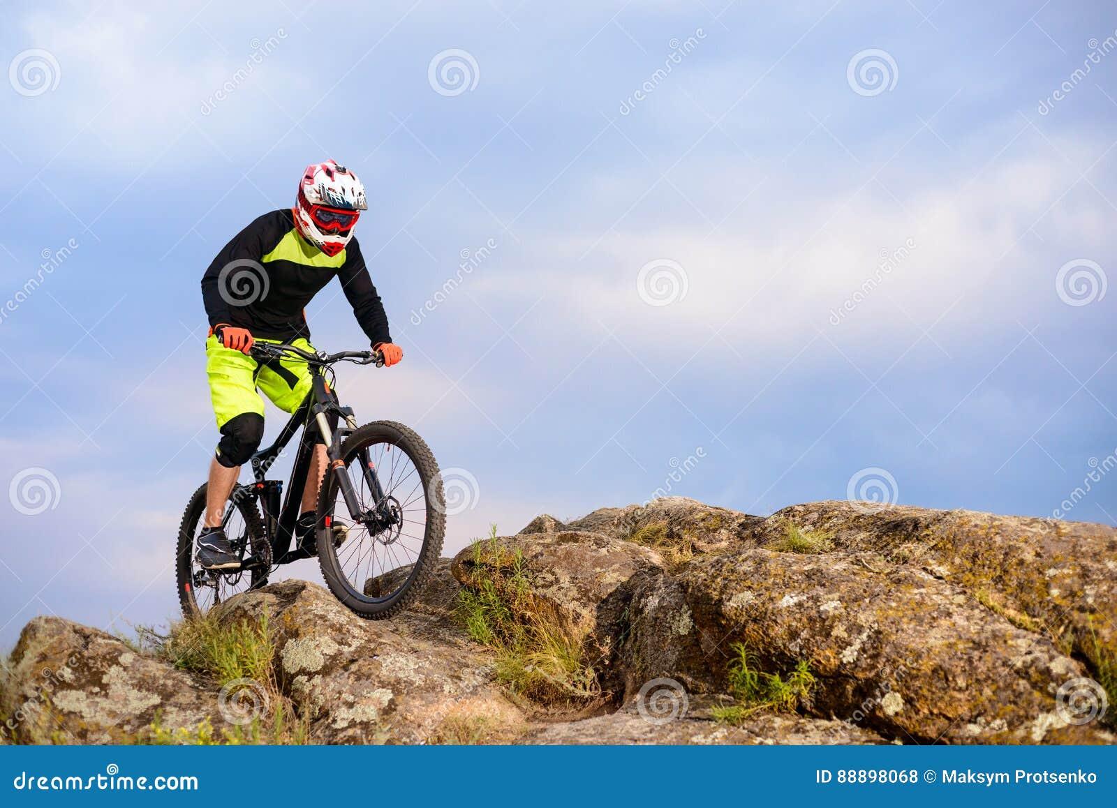 Επαγγελματικός ποδηλάτης που οδηγά το ποδήλατο στην κορυφή του βράχου Ακραία αθλητική έννοια Διάστημα για το κείμενο