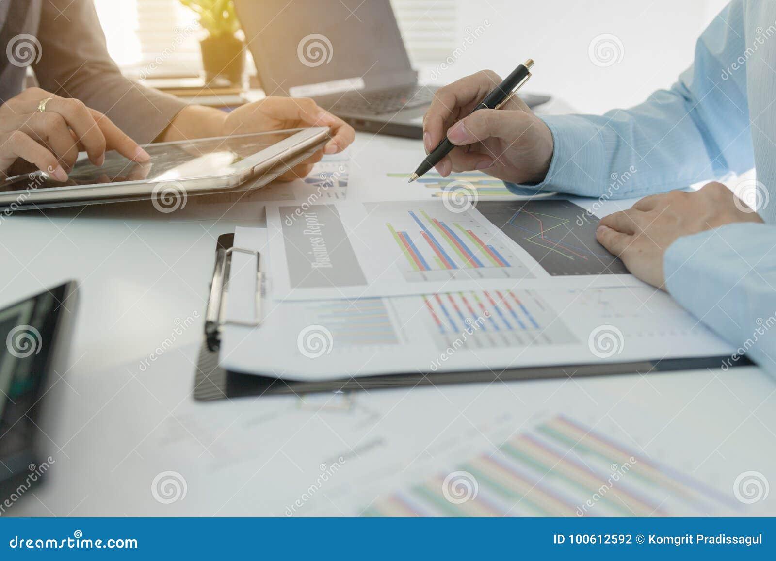 Επενδυτών εκτελεστικά συζήτησης στοιχεία γραφικών παραστάσεων σχεδίων οικονομικά όσον αφορά τον πίνακα γραφείων με το lap-top και