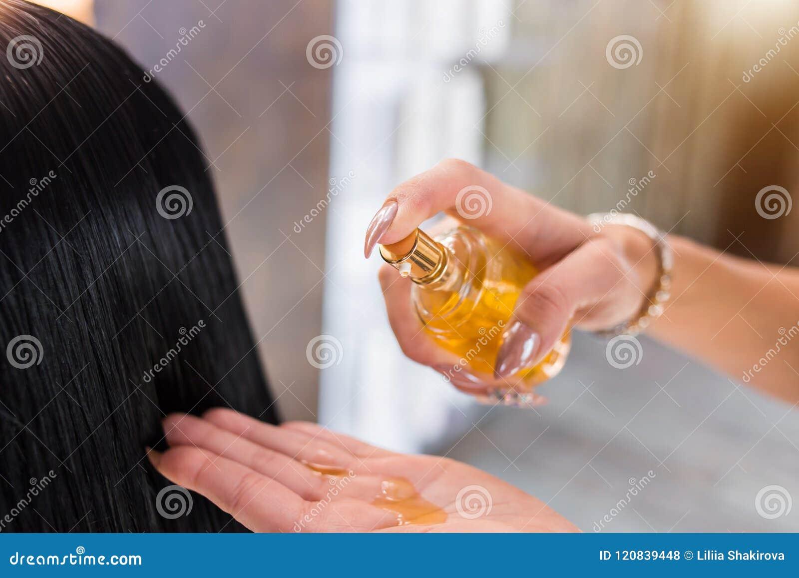 Επεξεργασία τρίχας πετρελαίου γυναίκας SPA, σαλόνι ομορφιάς Προσοχή τρίχας στο σύγχρονο σαλόνι SPA η γυναίκα κομμωτών εφαρμόζει μ