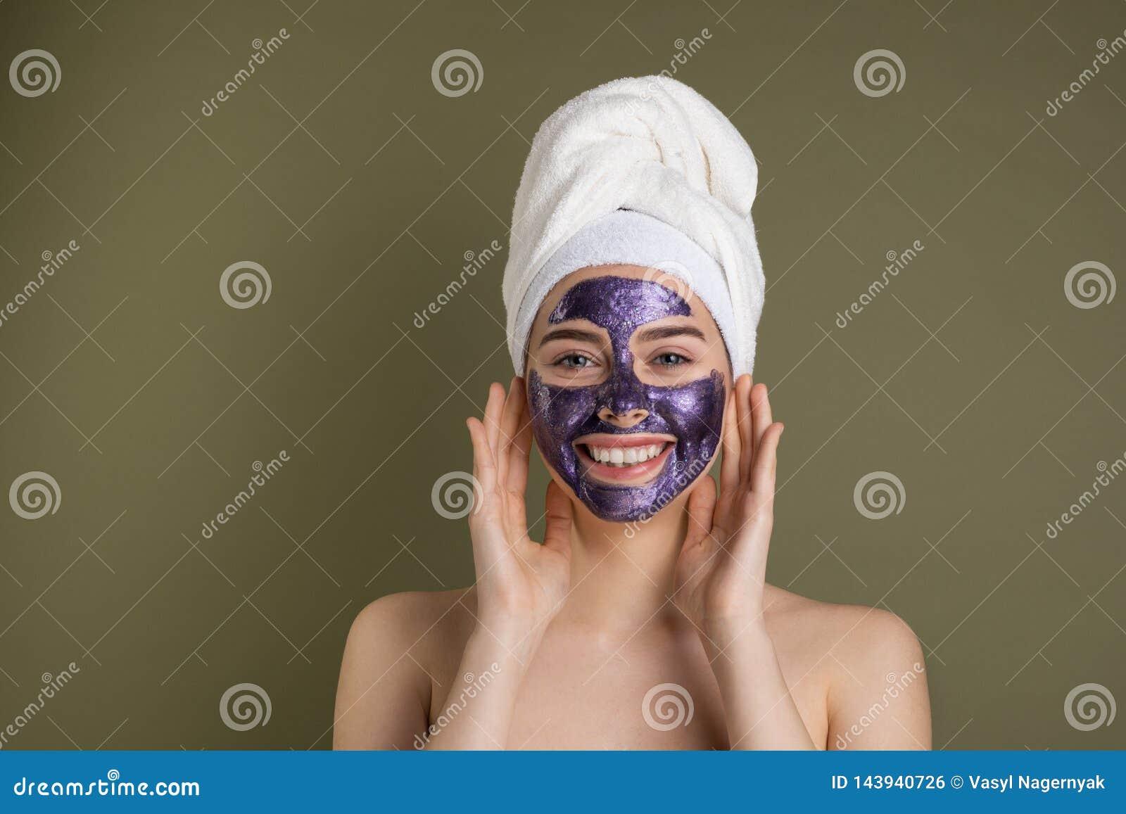 Επεξεργασίες προσοχής και ομορφιάς προσώπου Ευτυχής γυναίκα με την πορφυρή ενυδατική μάσκα υφασμάτων στο πρόσωπό της