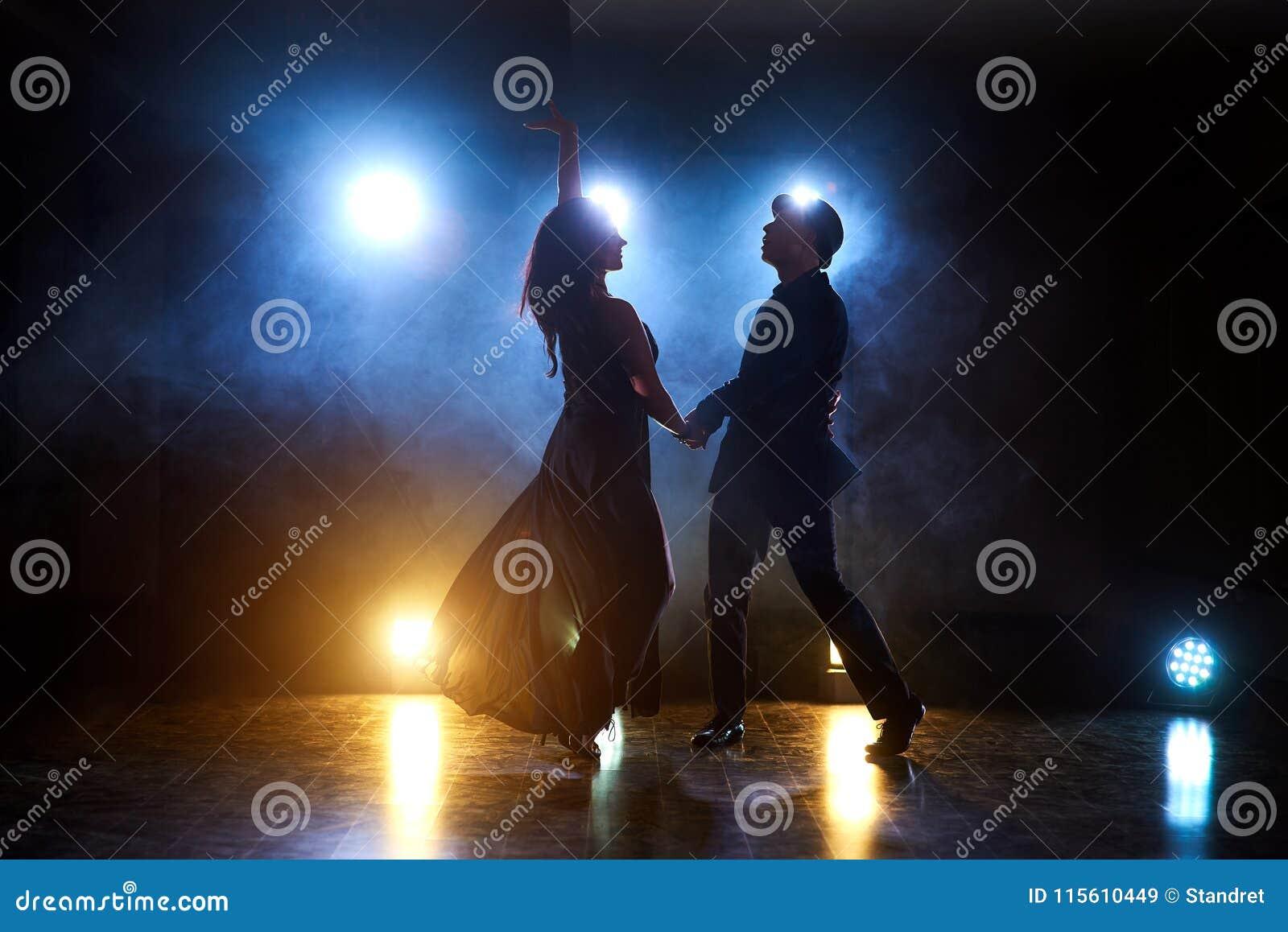 Επιδέξιοι χορευτές που αποδίδουν στο σκοτεινό δωμάτιο κάτω από το φως και τον καπνό συναυλίας Αισθησιακό ζεύγος που εκτελεί έναν