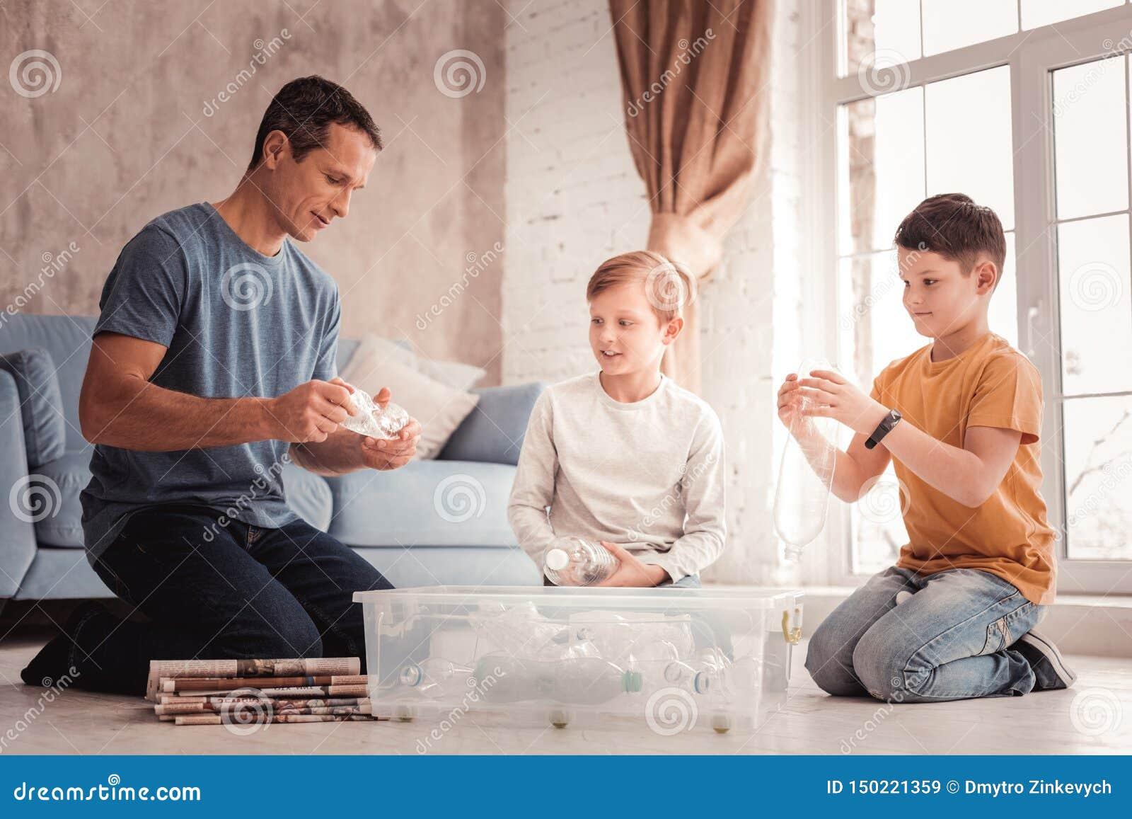 Επιμελής ενθαρρύνετε τον πατέρα που λέει στους γιους του για την ανακύκλωση απορριμμάτων