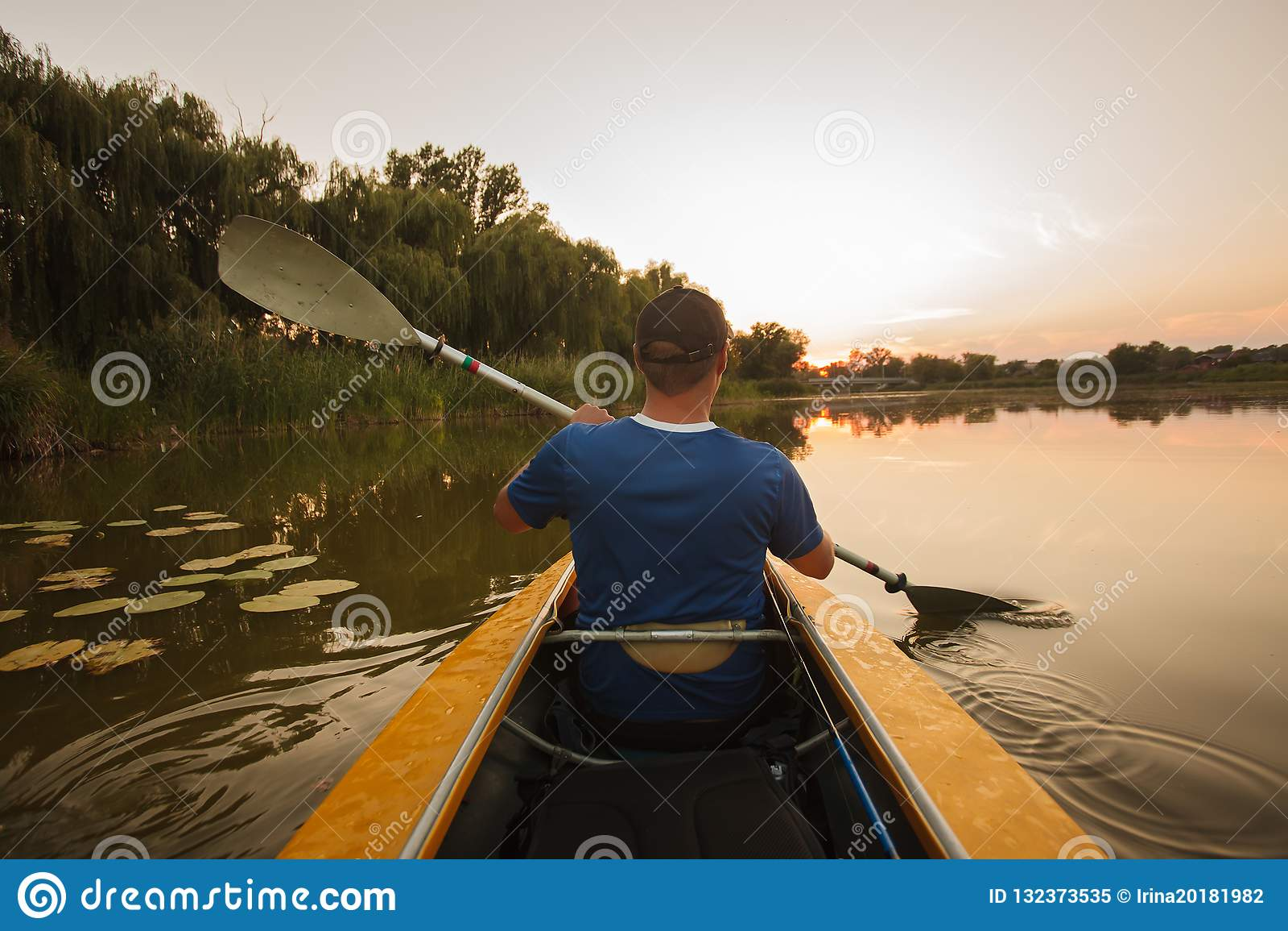 Επιπλέοντα σώματα ατόμων στο καγιάκ αθλητισμός νερού ηλιοβασιλέματος ατόμων καγιάκ