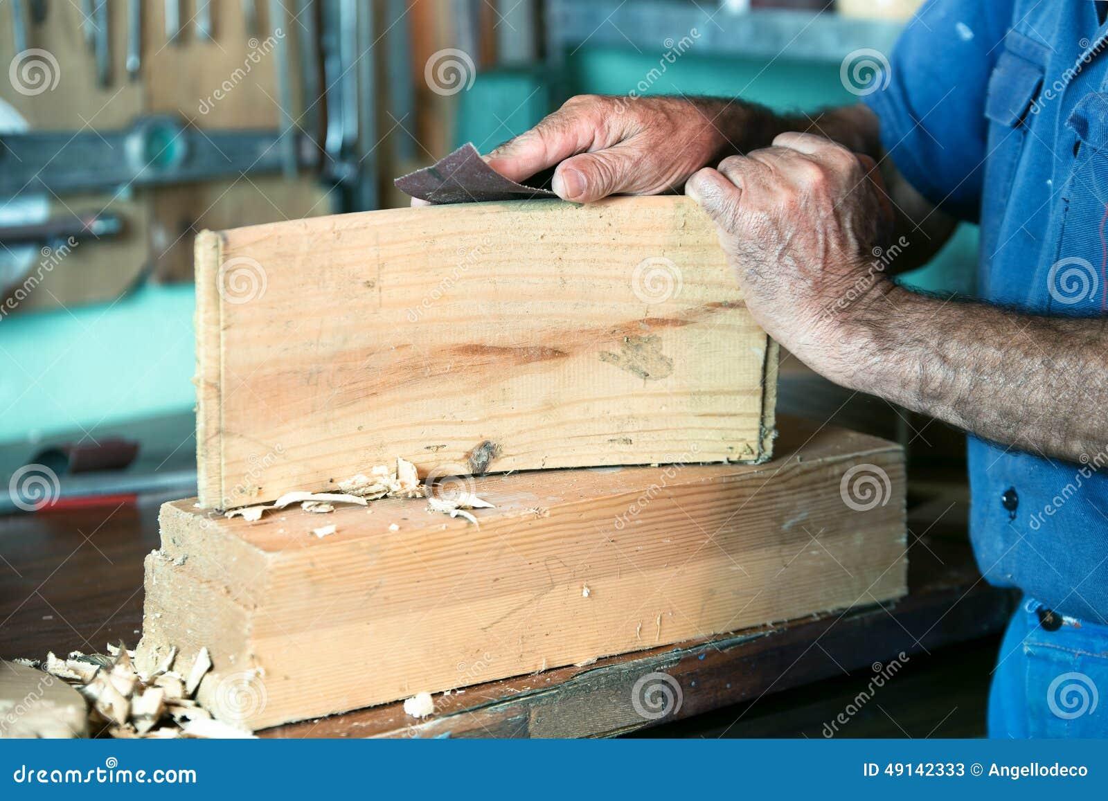Επιπλοποιός που εργάζεται με το γυαλόχαρτο στον πάγκο στο γκαράζ στο ho