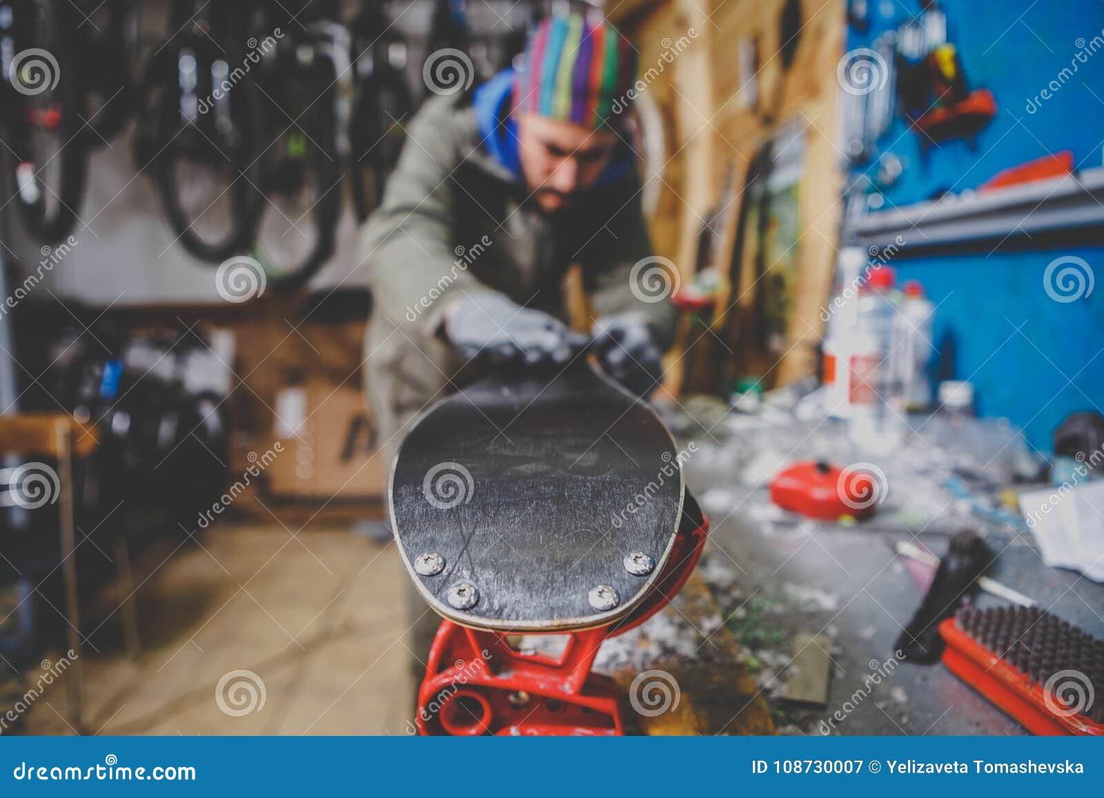 Επισκευές θέματος και συντήρηση των σκι Ο άνδρας εργαζόμενος επισκευάζει τα ενδύματα εργασίας, εφαρμόζοντας το κερί στην επιφάνει