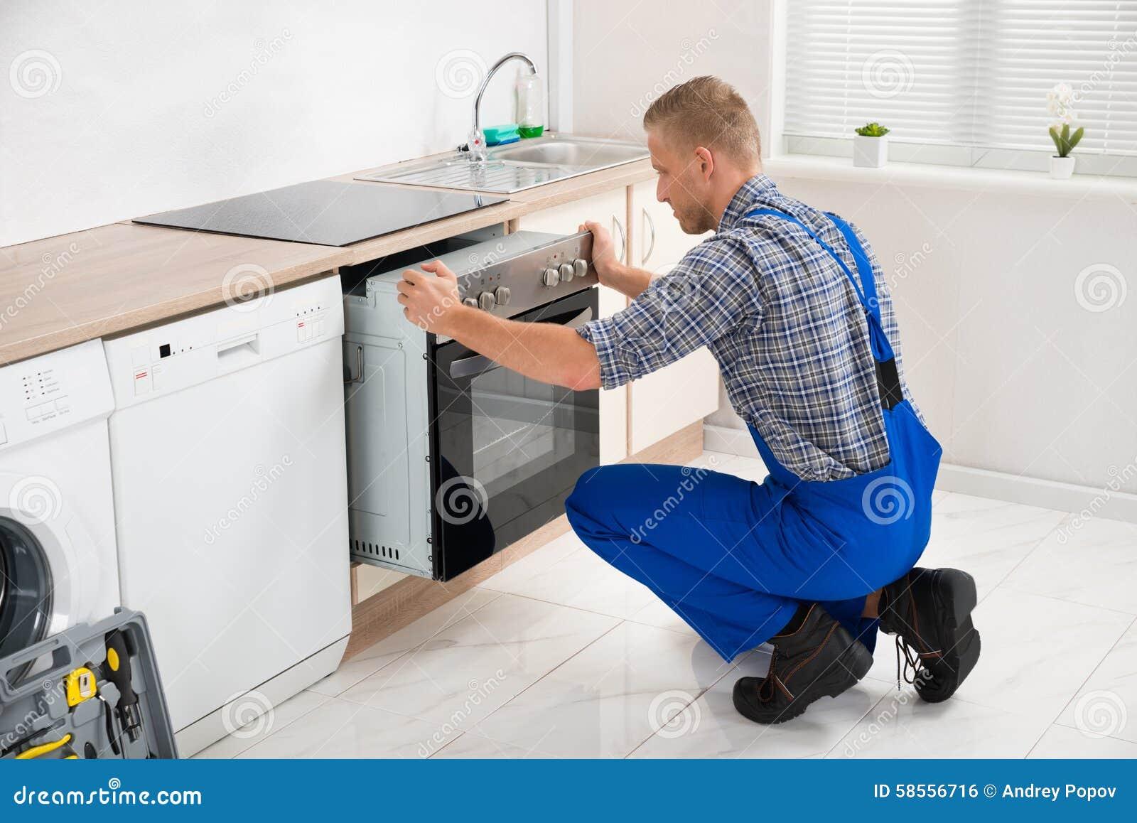 Επισκευαστής που επισκευάζει το φούρνο