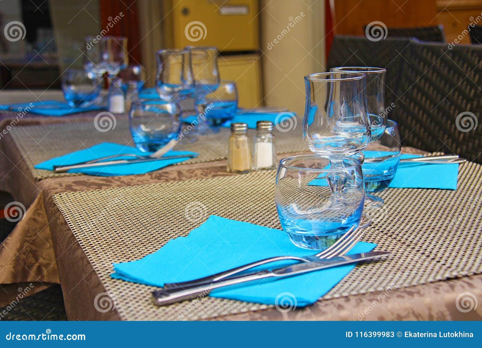 Επιτραπέζια ρύθμιση - μαχαίρι και δίκρανο, goblets γυαλιού, μπλε πετσέτες στο β