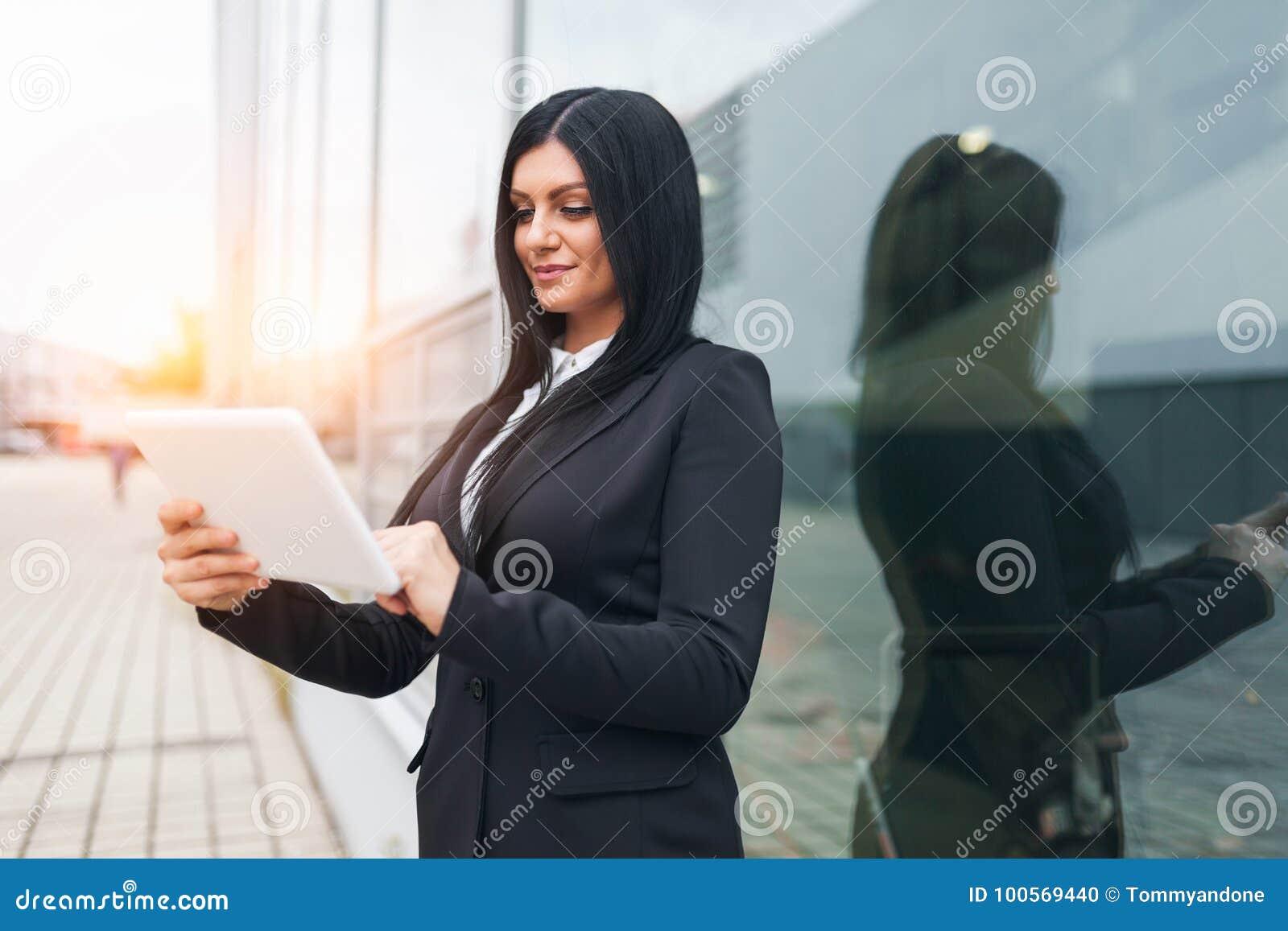 Επιτυχής επιχειρησιακή γυναίκα που εργάζεται με την ταμπλέτα σε μια αστική ρύθμιση
