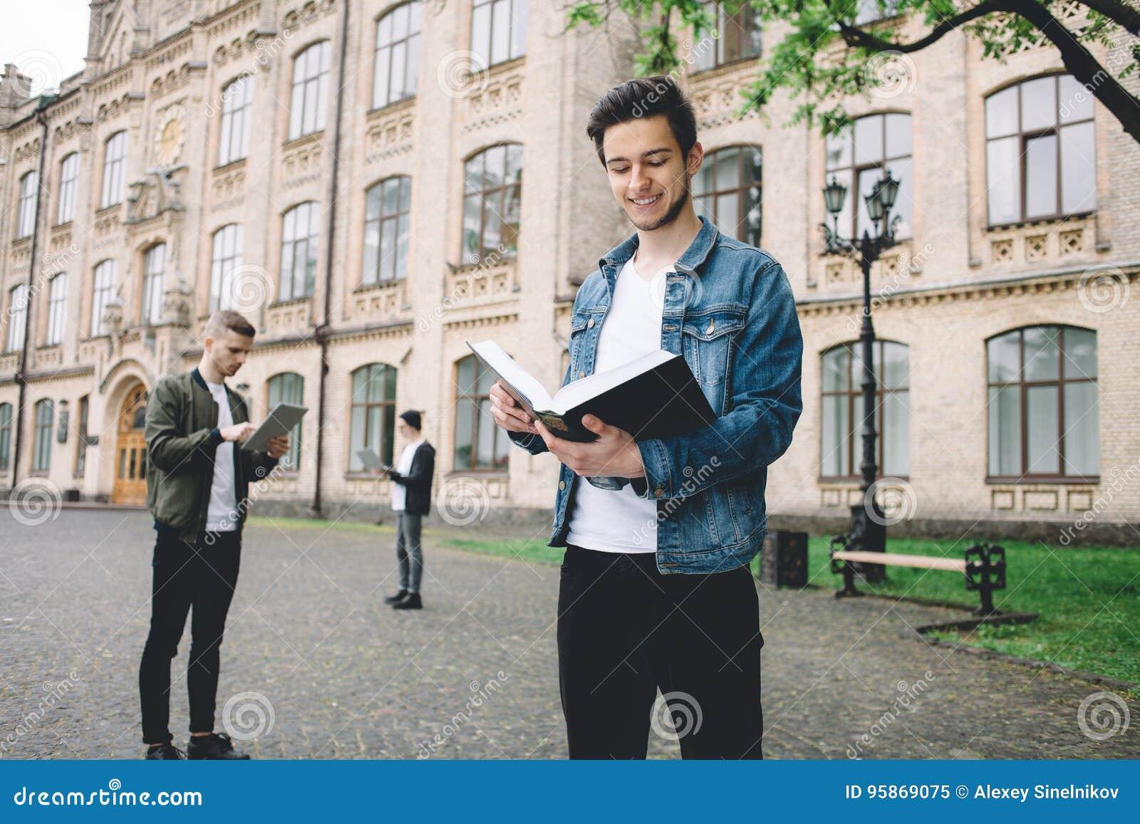 Επιτυχείς ευτυχείς σπουδαστές που στέκονται κοντά στην πανεπιστημιούπολη ή το πανεπιστήμιο έξω