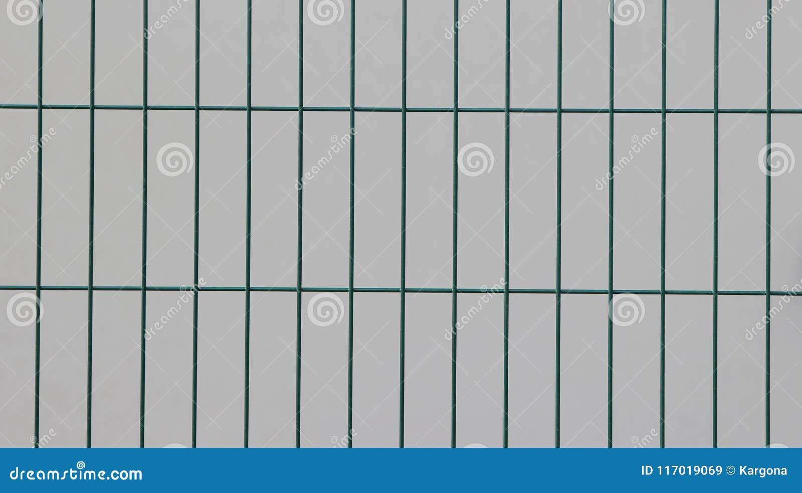 Επιφάνεια ενός ενωμένου στενά φράκτη καλωδίων με τα ορθογώνια στοιχεία που χρωματίζονται σε πράσινο μπροστά από έναν άσπρο τοίχο