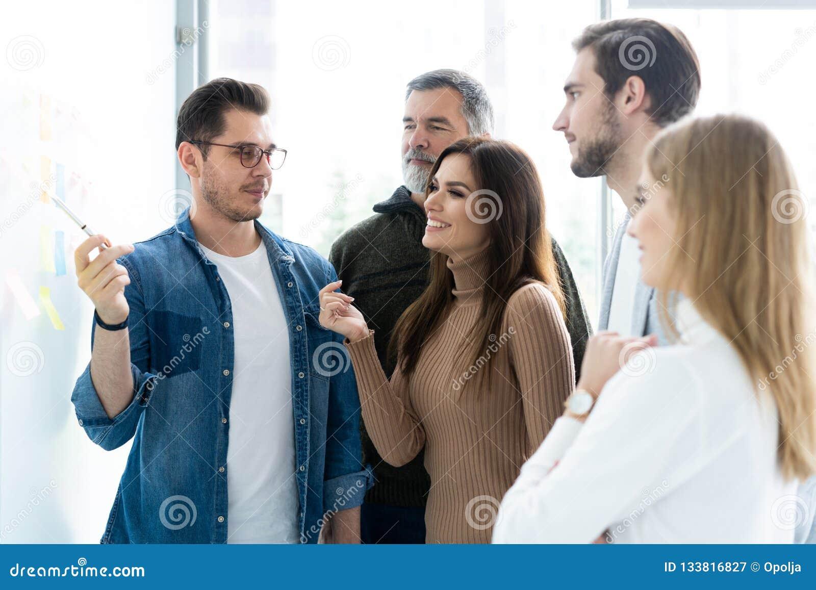 Επιχείρηση, εκπαίδευση και έννοια γραφείων - επιχειρησιακή ομάδα με τον πίνακα κτυπήματος στην αρχή συζητώντας κάτι