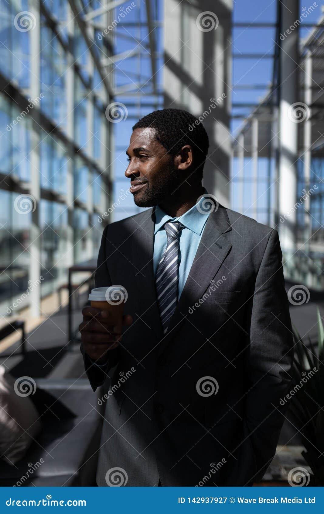 Επιχειρηματίας αφροαμερικάνων με το φλυτζάνι καφέ που φαίνεται μακριά στην αρχή