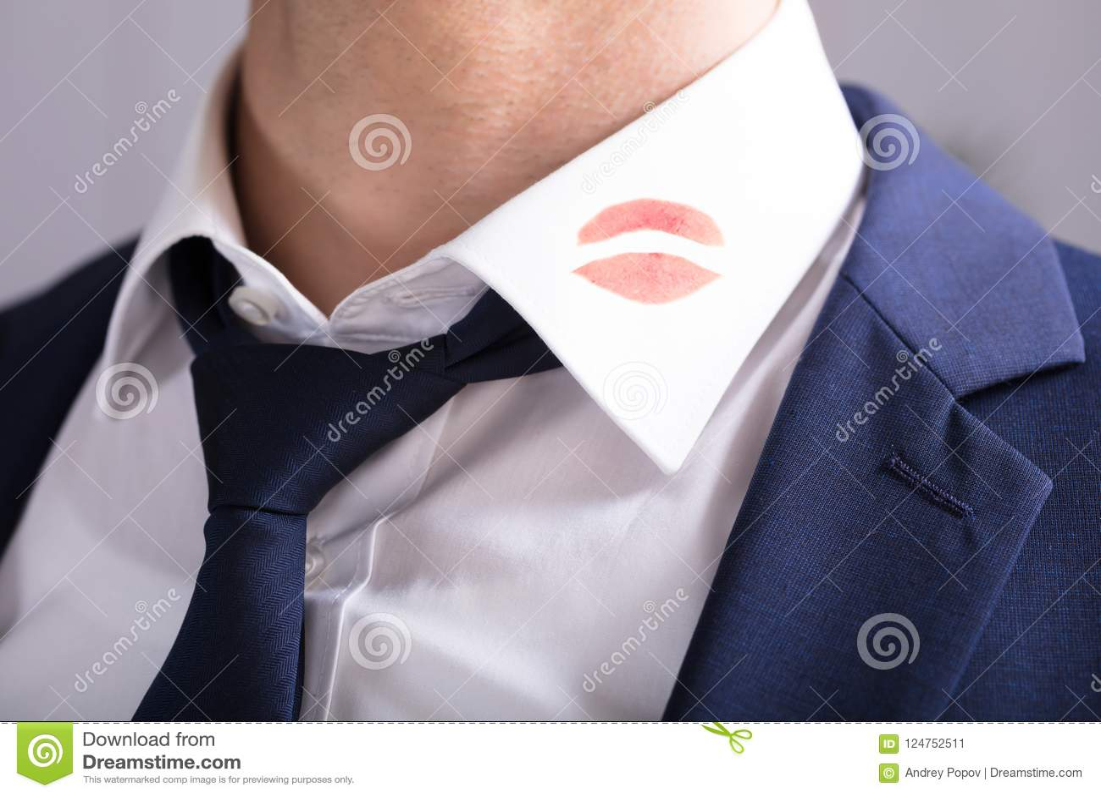 Επιχειρηματίας με τα σημάδια φιλιών κραγιόν στο περιλαίμιο πουκάμισων ` s