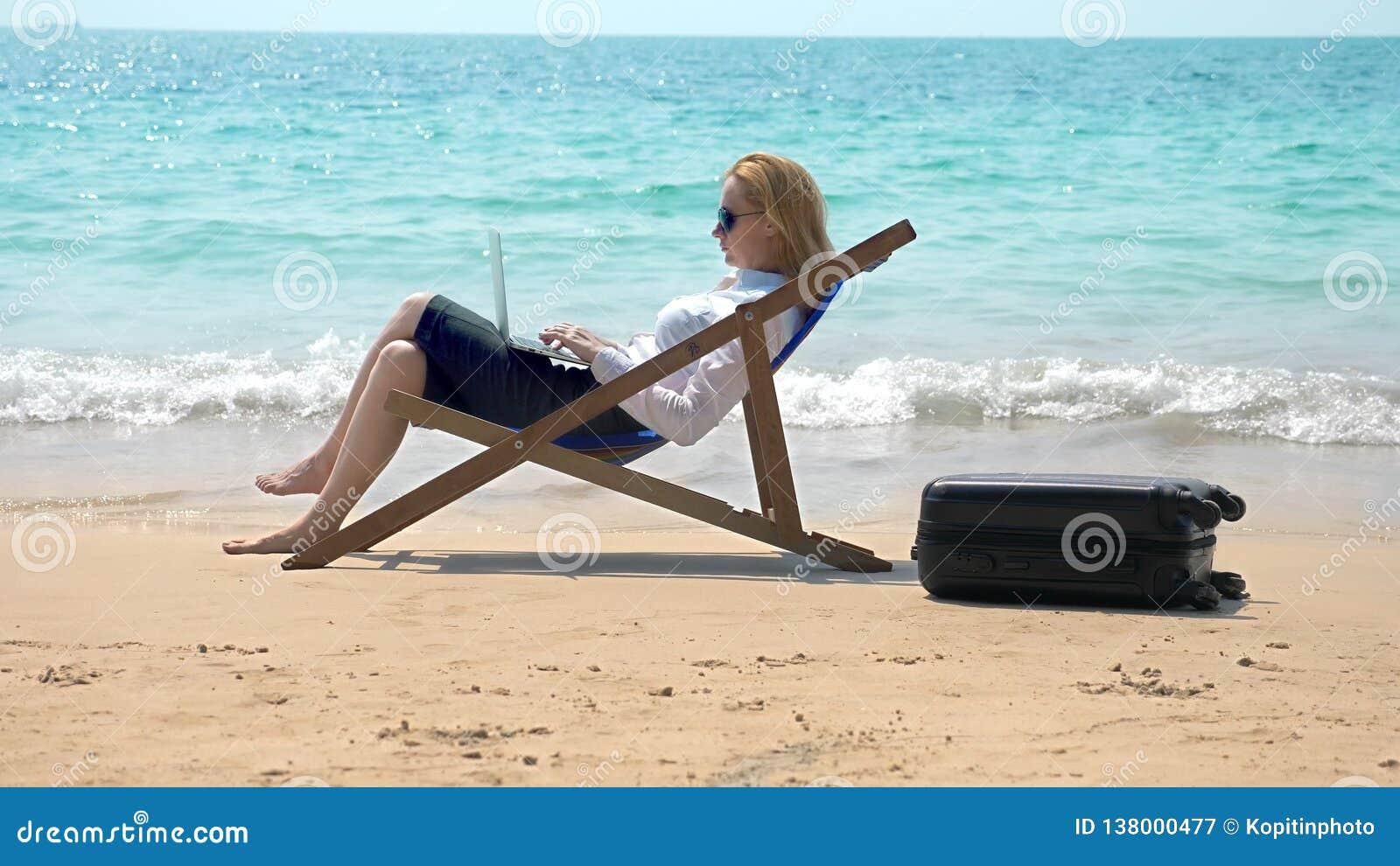 Επιχειρηματίας που εργάζεται σε ένα lap-top καθμένος σε έναν αργόσχολο θαλασσίως σε μια άσπρη αμμώδη παραλία ανεξάρτητος ή workah