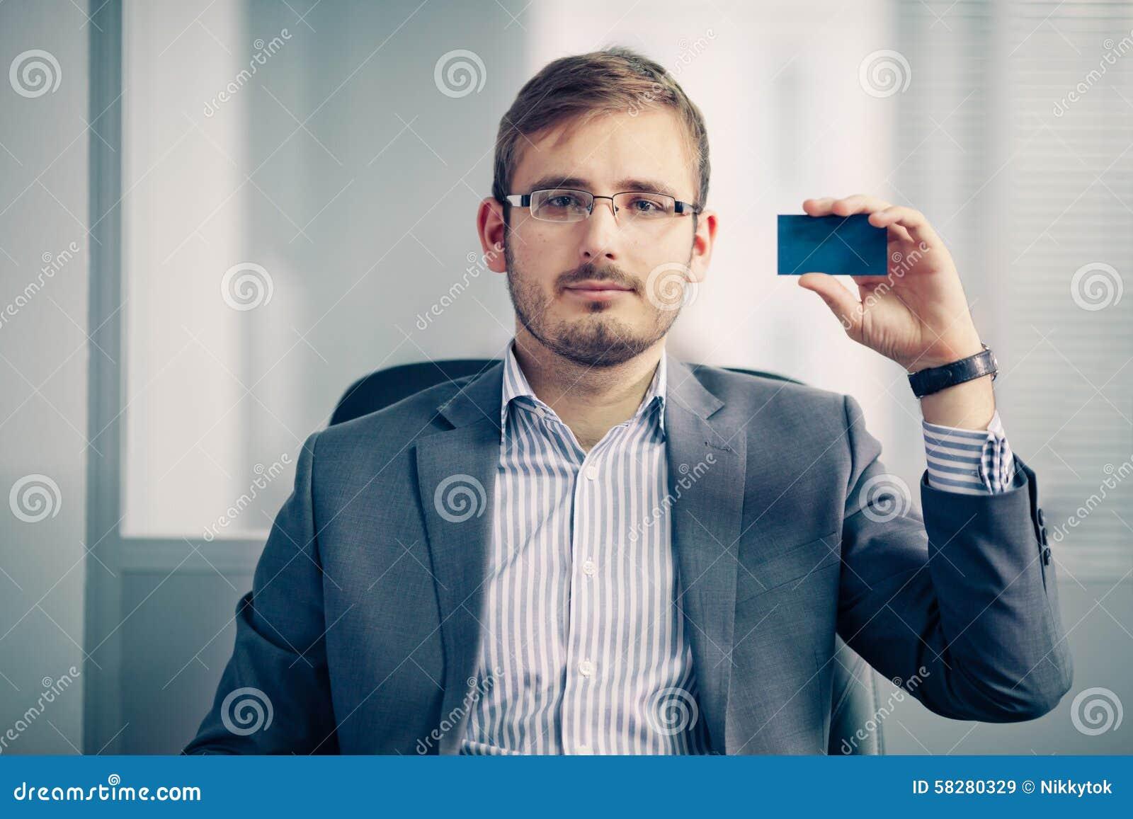 Επιχειρηματίας που κρατά την κενή επαγγελματική κάρτα στο γραφείο