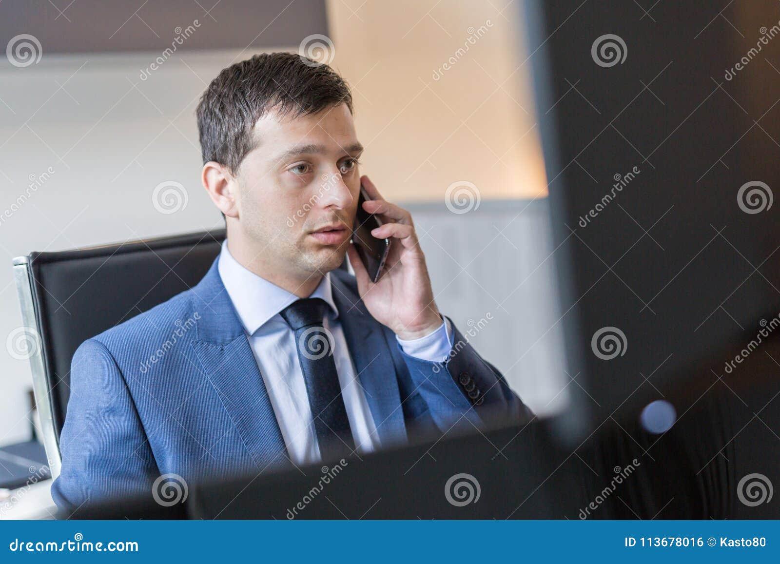 Επιχειρηματίας που μιλά στο κινητό τηλέφωνο προσέχοντας τα διαγράμματα και τις αναλύσεις στοιχείων στις πολλαπλάσιες οθόνες υπολο