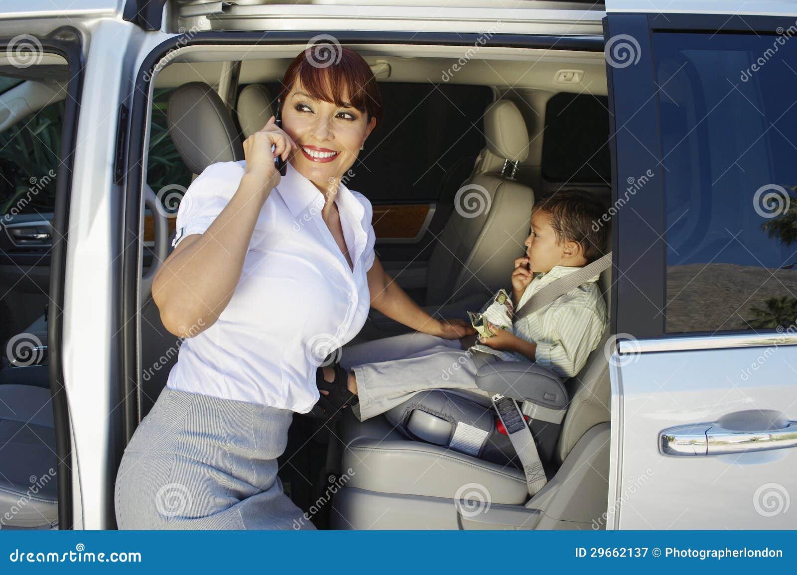 Επιχειρηματίας που χρησιμοποιεί το τηλέφωνο κυττάρων με τη συνεδρίαση γιων στο αυτοκίνητο