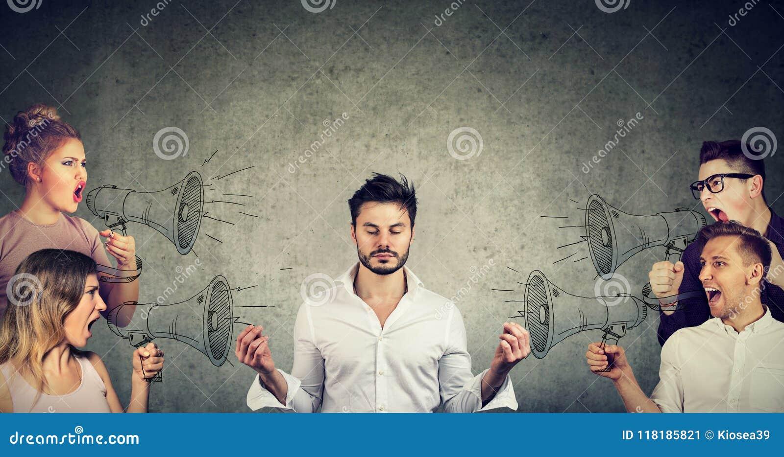 Επιχειρηματίας Meditating που δεν δίνει καμία προσοχή στο πλήθος των κραυγάζοντασων ?ν ανθρώπων