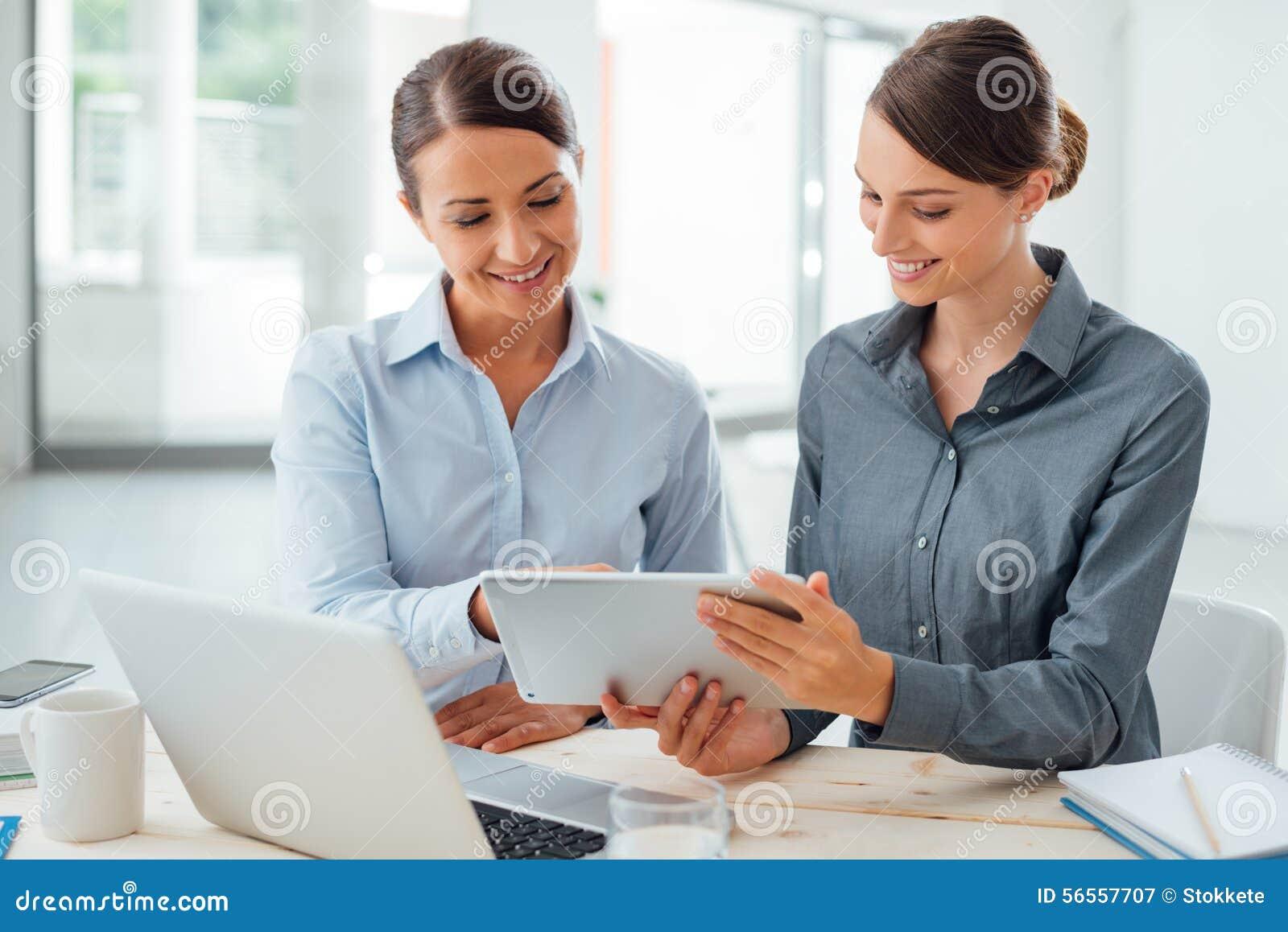 Download Επιχειρησιακές γυναίκες που εργάζονται μαζί σε μια ταμπλέτα Στοκ Εικόνα - εικόνα από διευθυντής, περιλαίμιο: 56557707