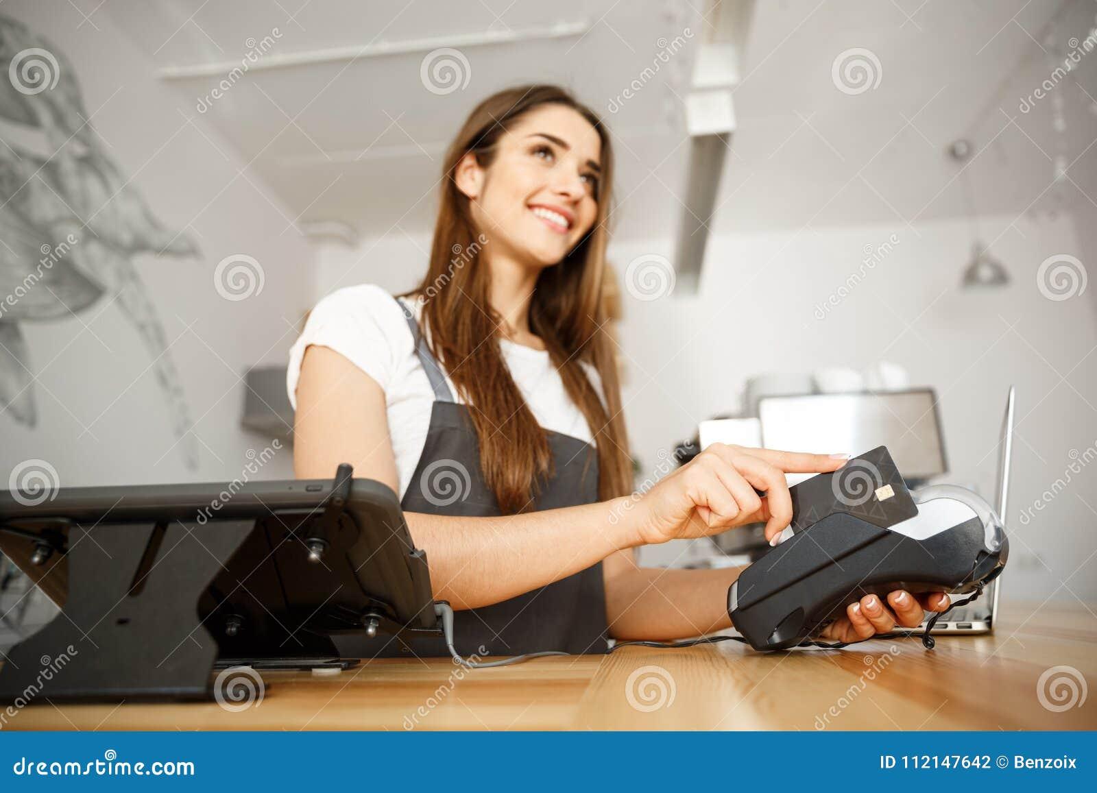 Επιχειρησιακή έννοια καφέ - όμορφο θηλυκό barista που δίνει την υπηρεσία πληρωμής για τον πελάτη με την πιστωτική κάρτα και το χα