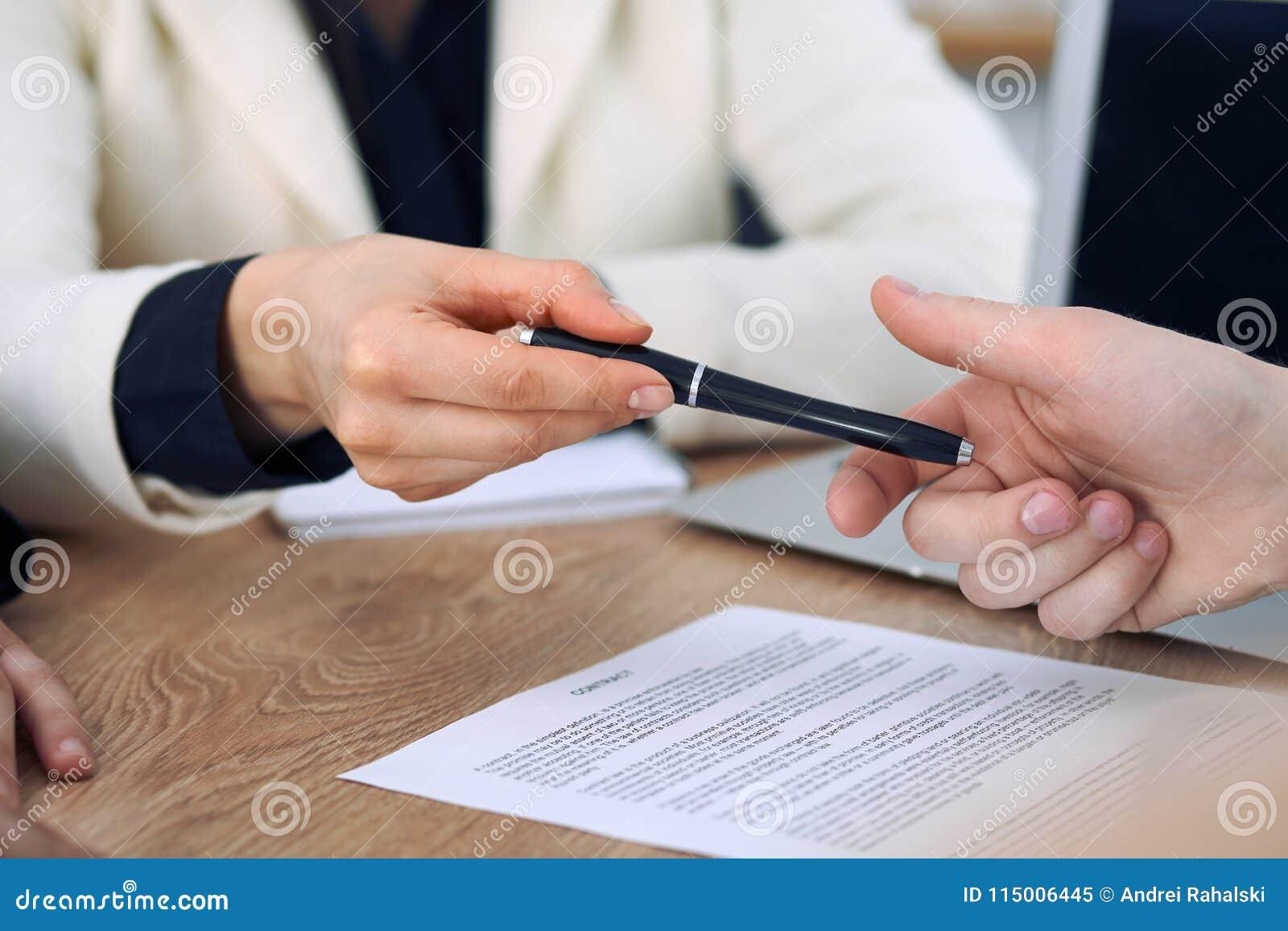 Επιχειρησιακή γυναίκα που δίνει τη μάνδρα στον επιχειρηματία έτοιμο να υπογράψει τη σύμβαση Επικοινωνία επιτυχίας στη συνεδρίαση