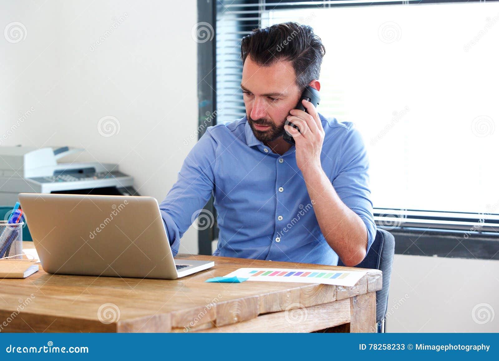 Επιχειρησιακό άτομο που εργάζεται στο lap-top και που μιλά στο κινητό τηλέφωνο
