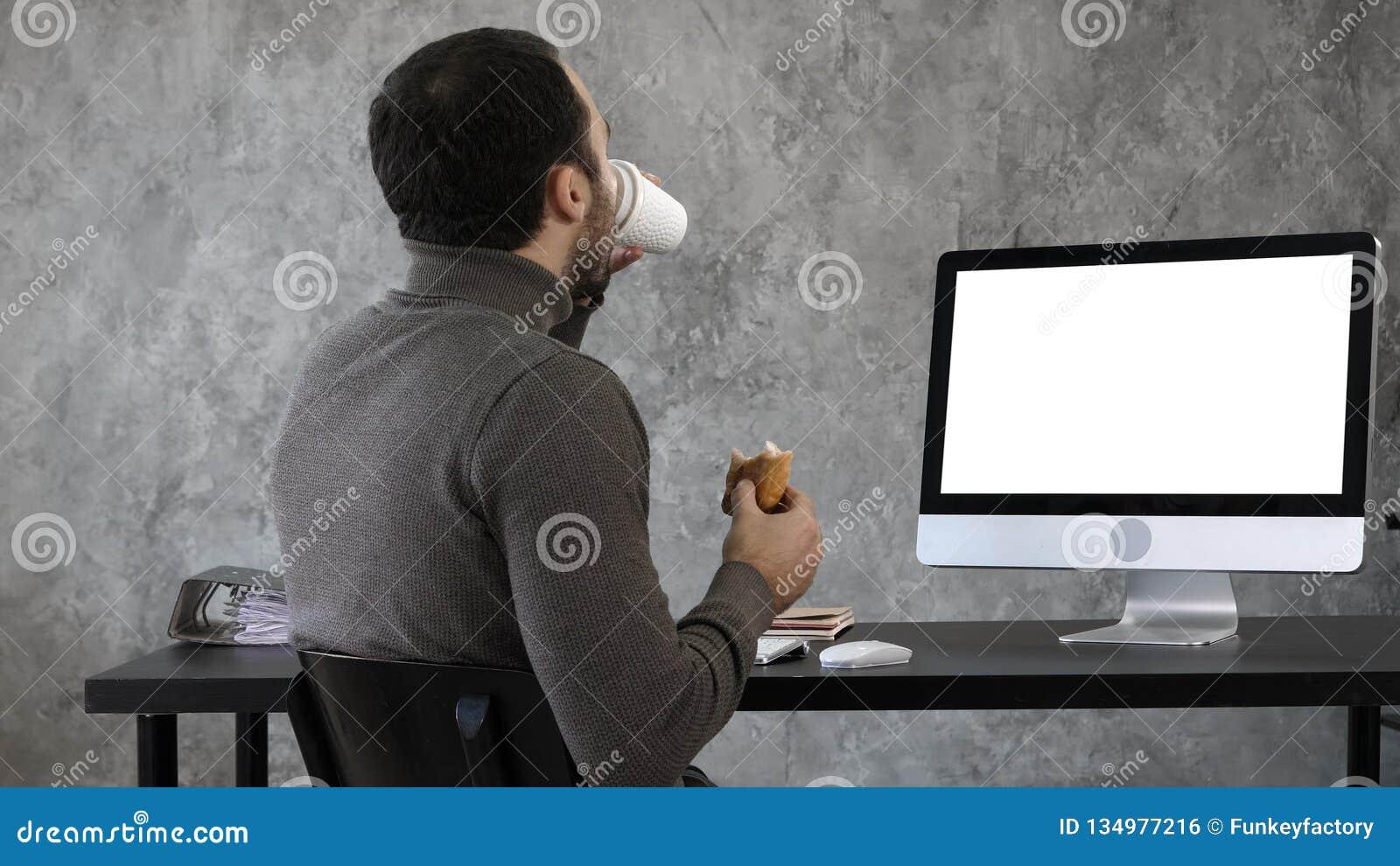 Επιχειρησιακό άτομο στο γραφείο που έχει το πρόγευμα, μεσημεριανό γεύμα και που προσέχει κάτι στη MAC, υπολογιστής Άσπρη παρουσία