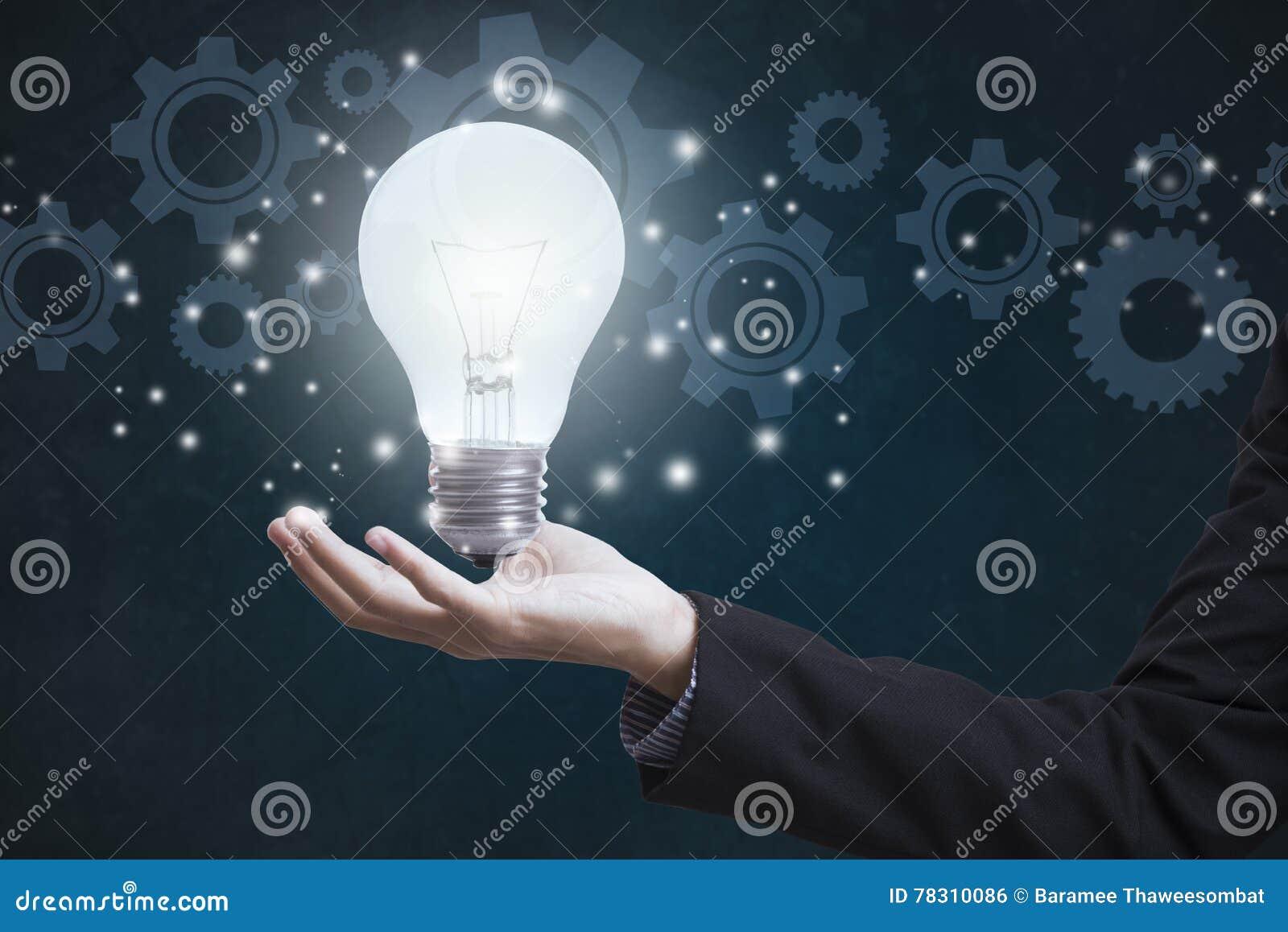 Επιχειρησιακό χέρι που κρατά την ηλεκτρική λάμπα φωτός με τις ρόδες εργαλείων