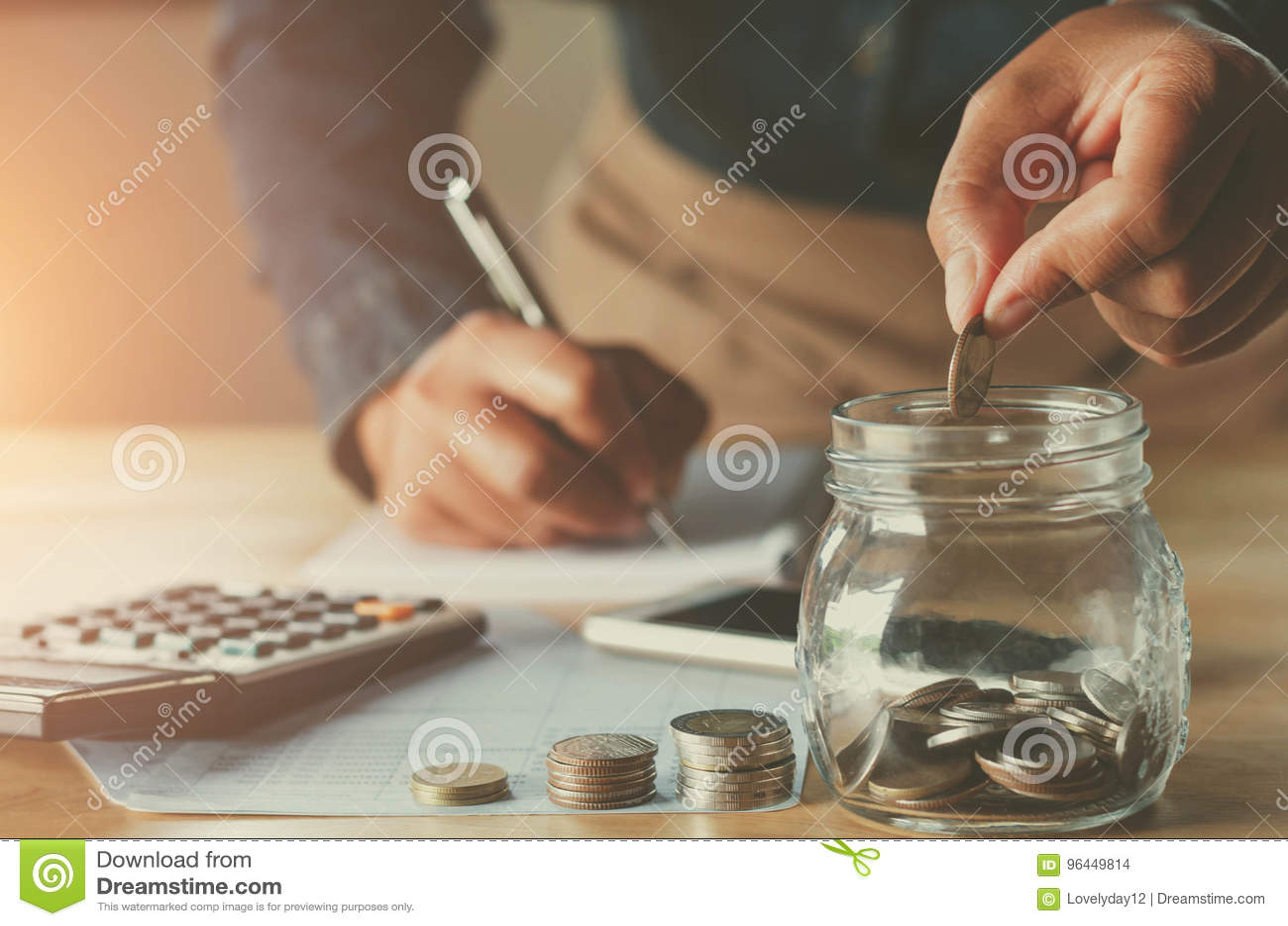 επιχειρησιακό accountin με τα χρήματα αποταμίευσης με το χέρι που υποβάλλει τα νομίσματα