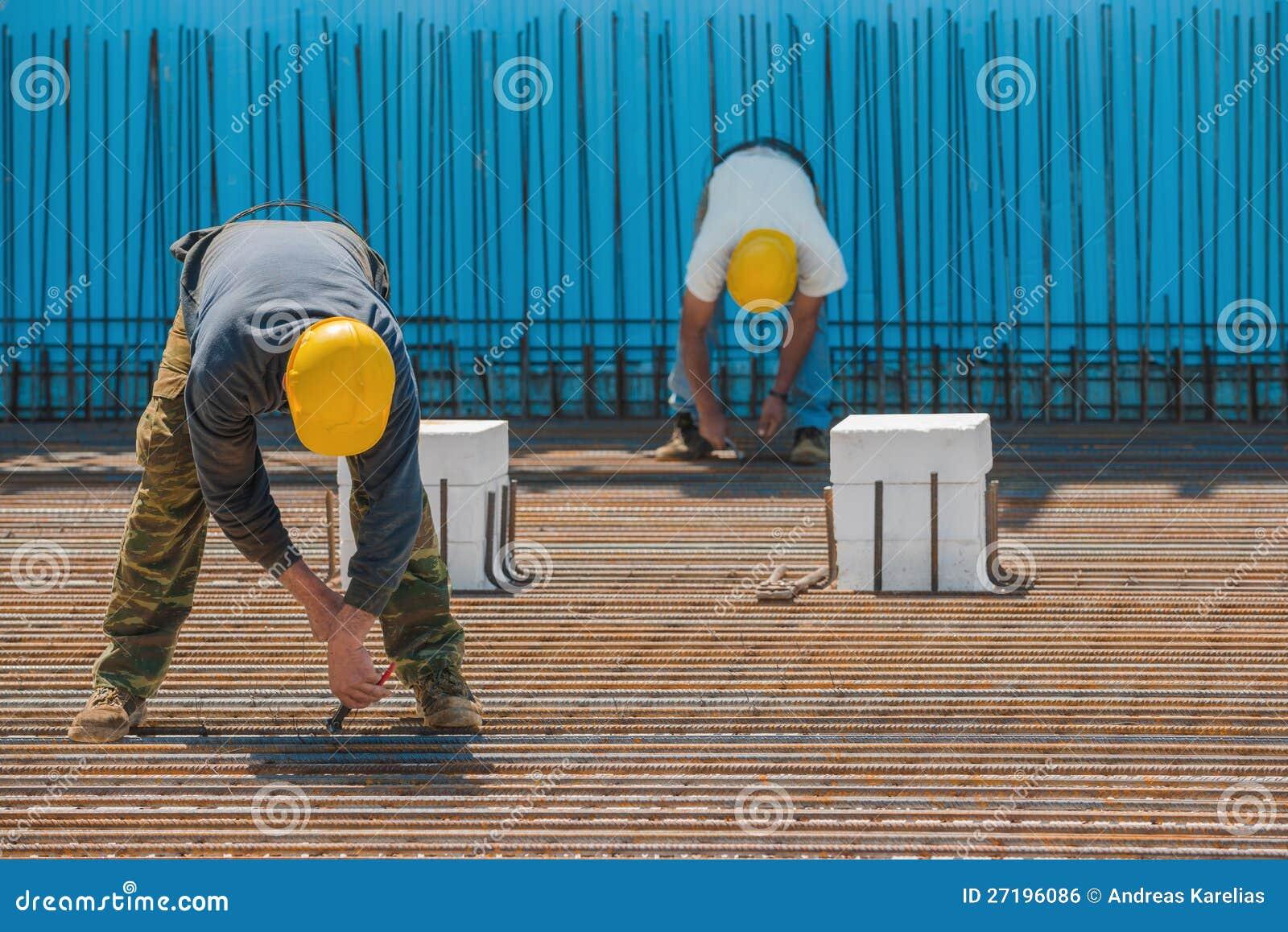 Εργάτες οικοδομών που δεσμεύουν τις ράβδους χάλυβα με τα καλώδια