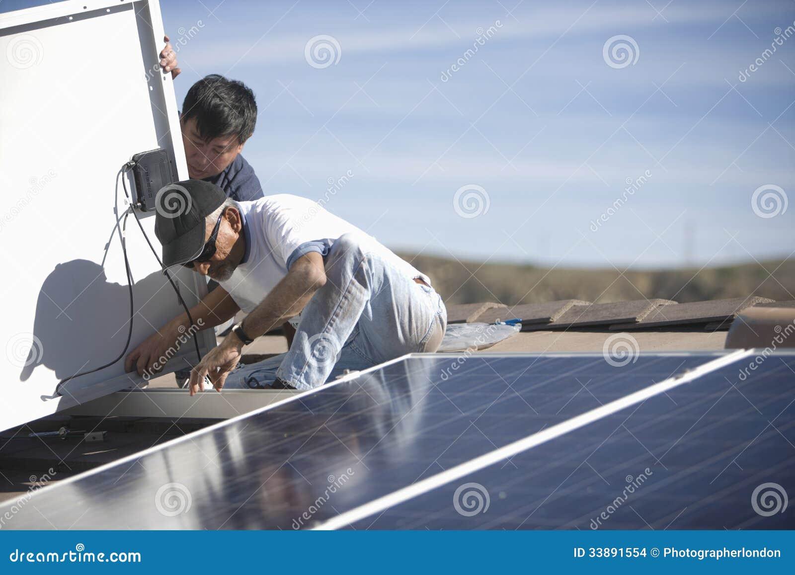 Εργαζόμενοι που καθορίζουν το ηλιακό πλαίσιο στην κορυφή στεγών