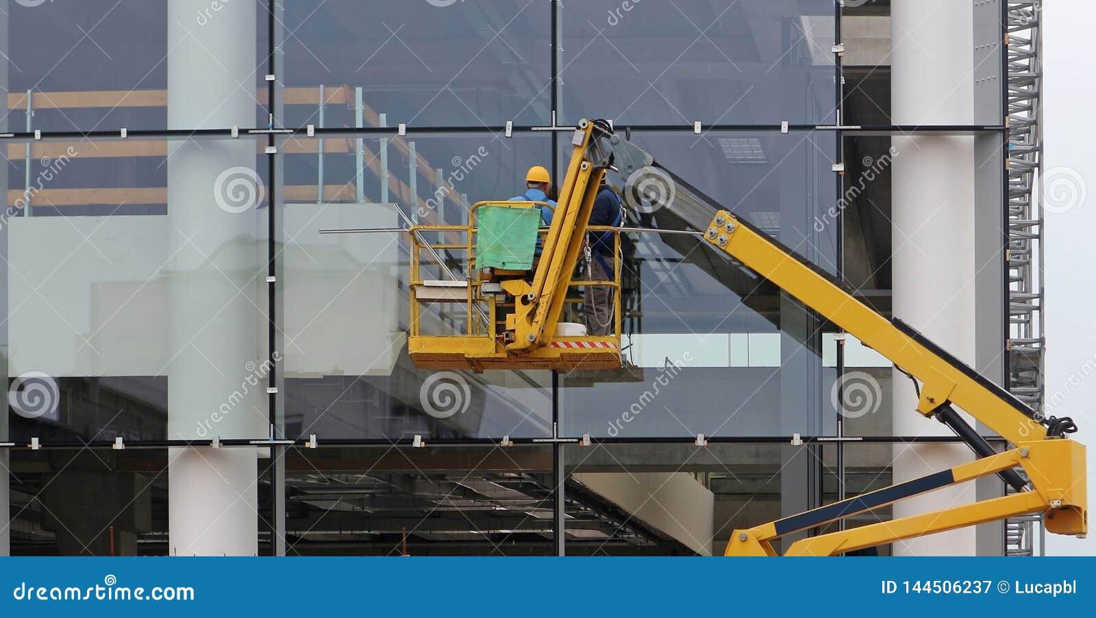 Εργαζόμενοι σε μια συλλεκτική μηχανή κερασιών Τελειώνουν την πρόσοψη γυαλιού ενός κτηρίου κάτω από την ανακαίνιση