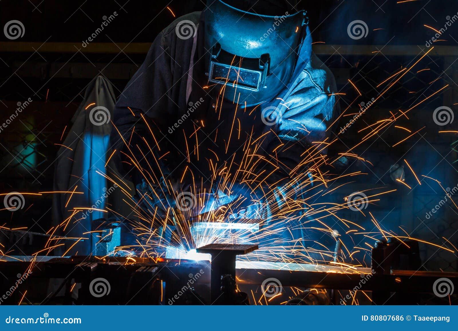 Εργαζόμενος με το προστατευτικό μέταλλο συγκόλλησης μασκών