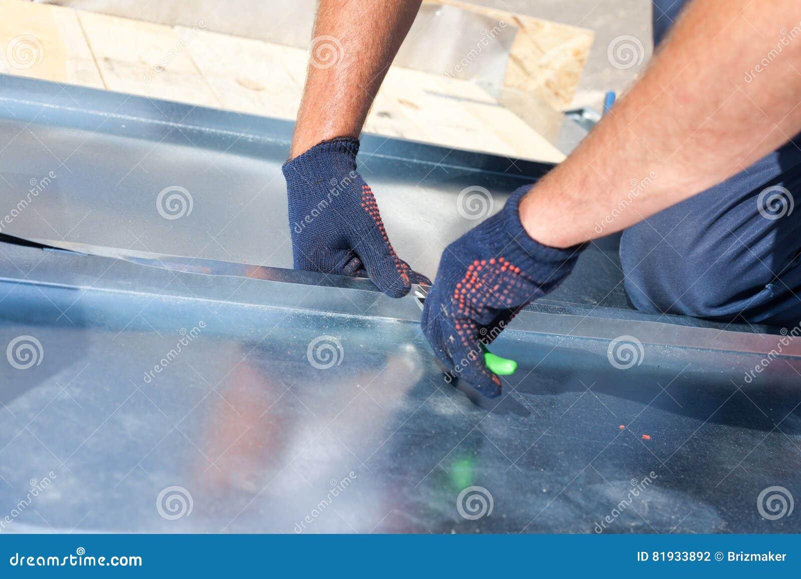 Εργαζόμενος οικοδόμων Roofer που τελειώνει διπλώνοντας ένα φύλλο μετάλλων που χρησιμοποιεί τις ειδικές πένσες με ένα μεγάλο επίπε