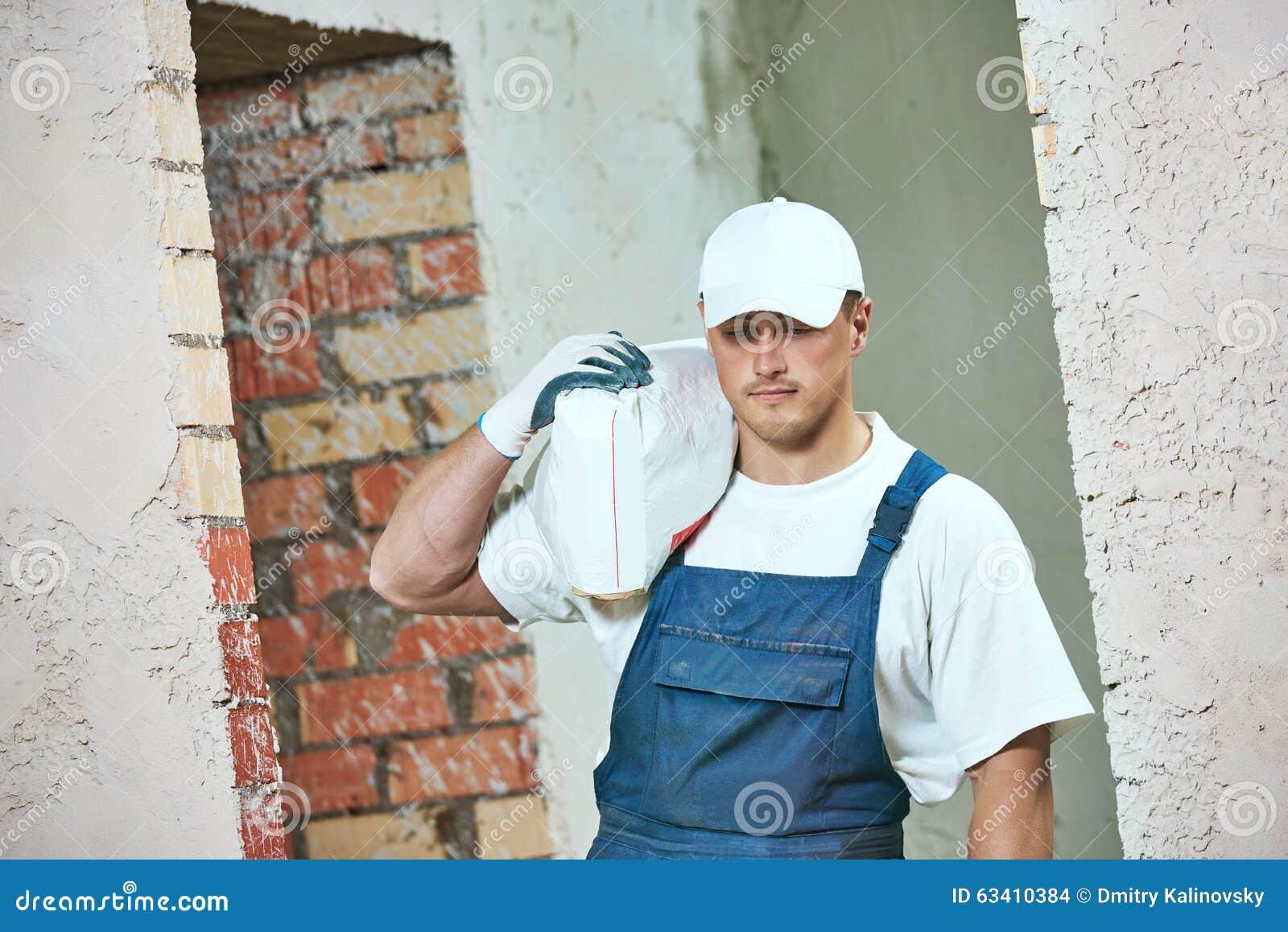 Εργαζόμενος που φέρνει την τσάντα του τσιμέντου